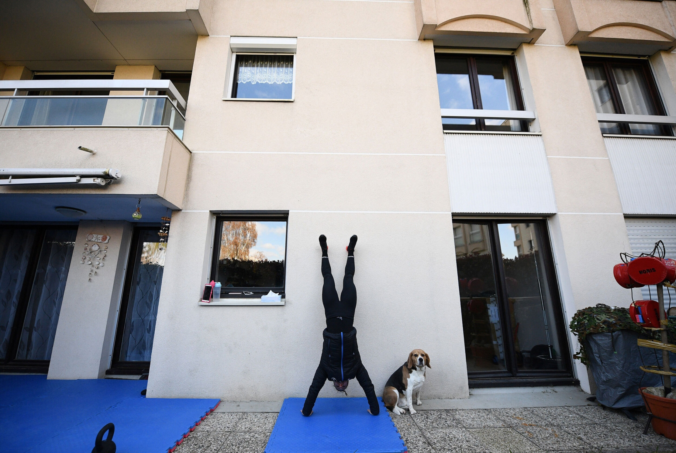 A woman on black gym clothes does a hand-stand on a mat in her backyard.