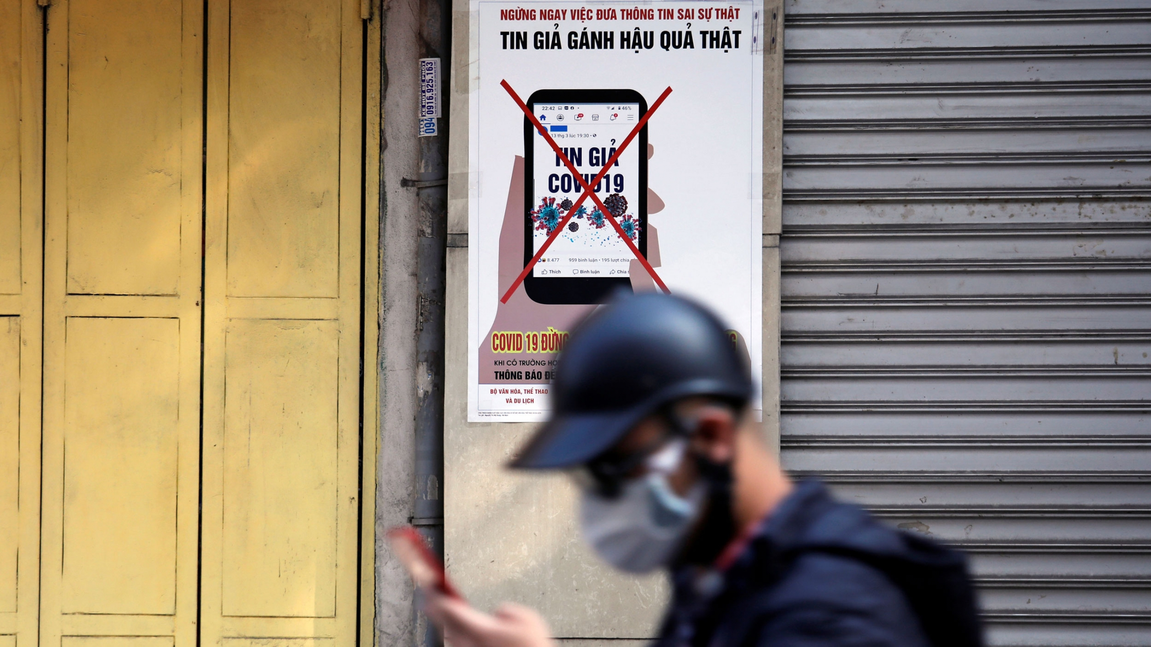 a man with a cellphone and a face mask walks in front of a sign in Vietnamese discouraging the spread of misinformation.