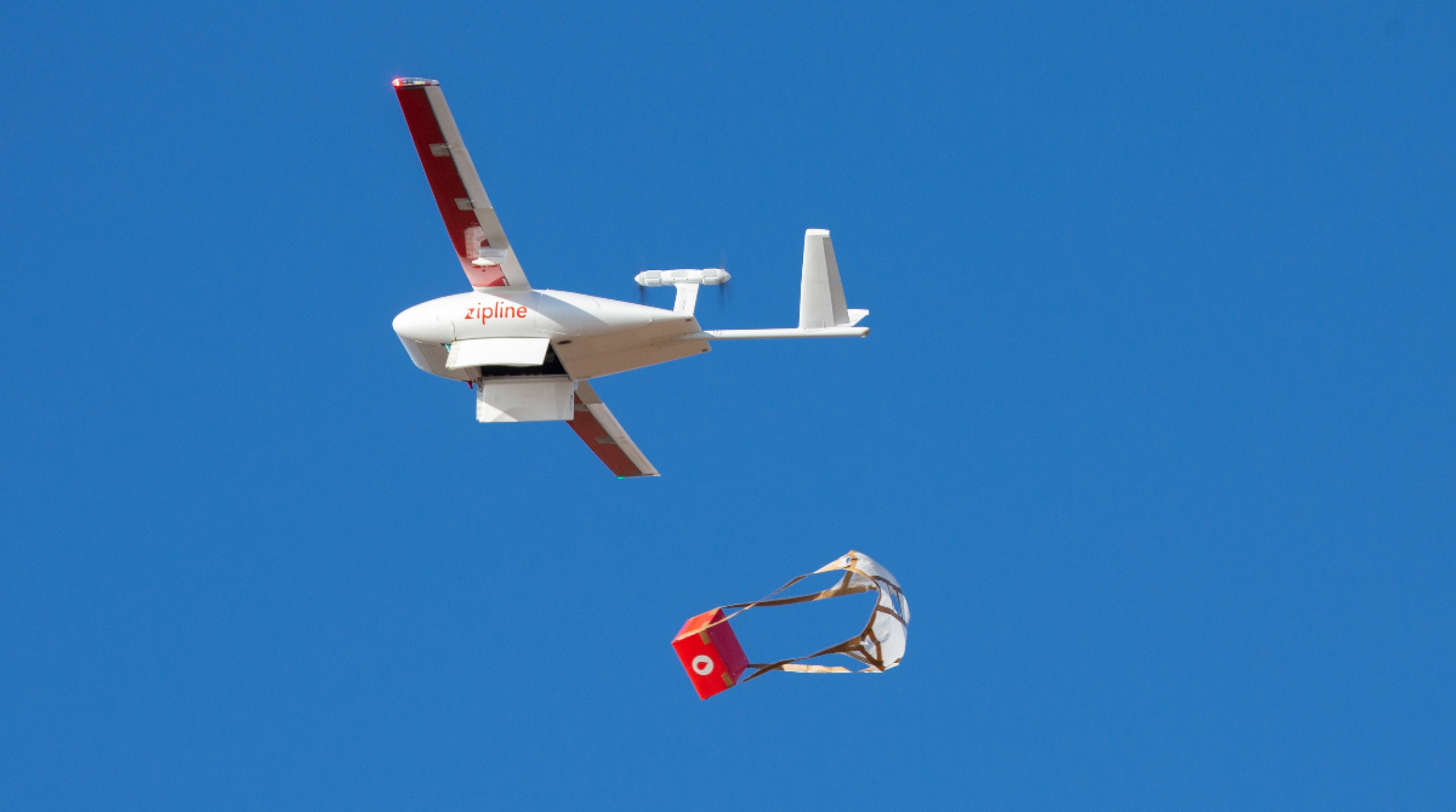 A small drone drops a red package