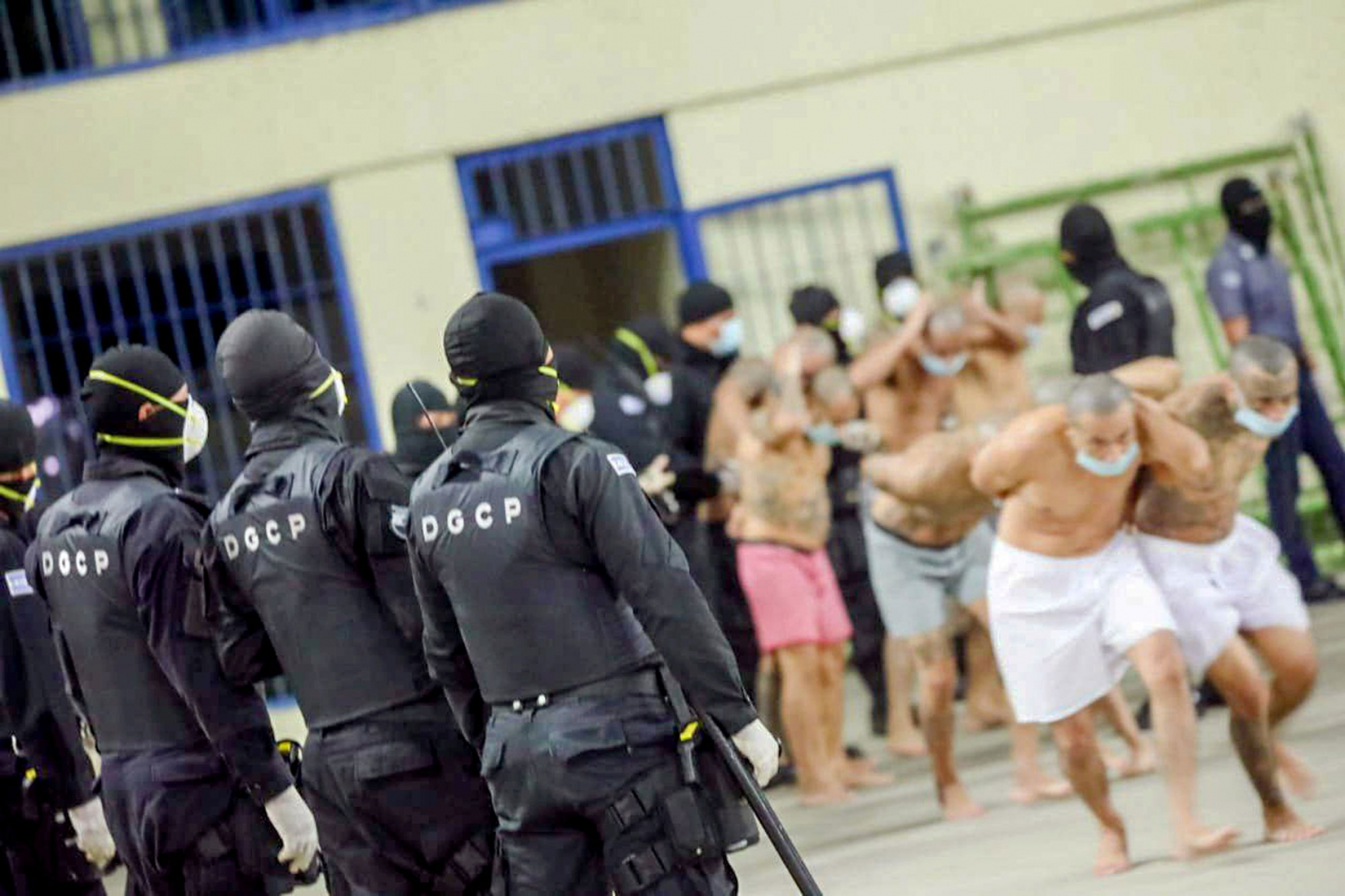 Inmates are shown at Izalco jail in the distance and walking with several armed guards in the nearground.