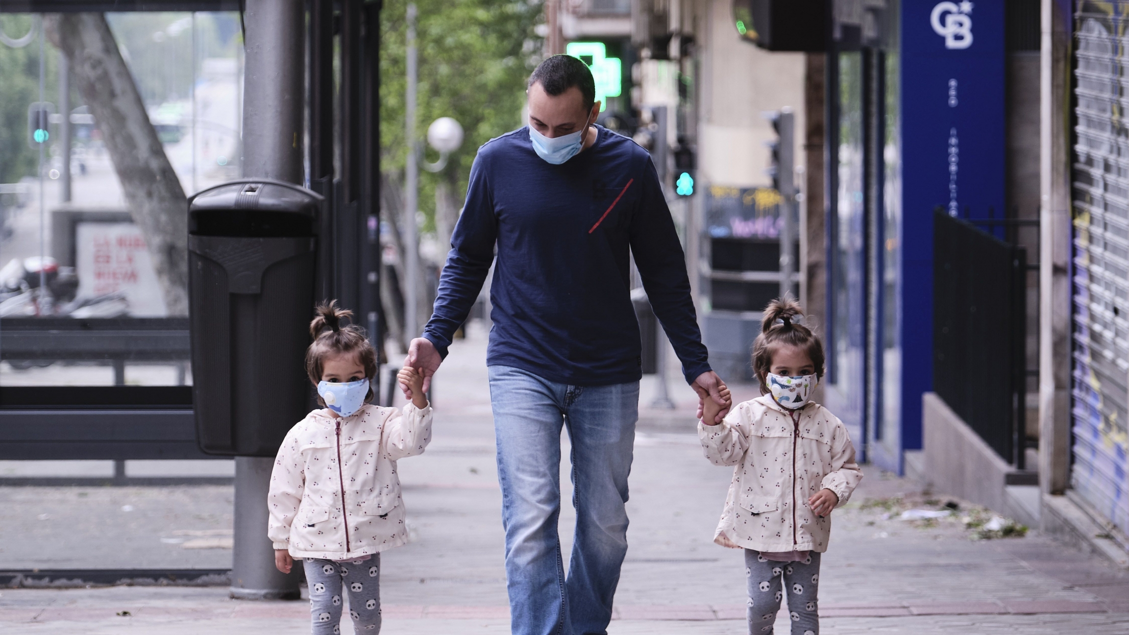 José Valdes takes his twin daughters out for a walk in Madridon the day Spain liftsrestrictions on children outdoors due to the coronavirus pandemic.
