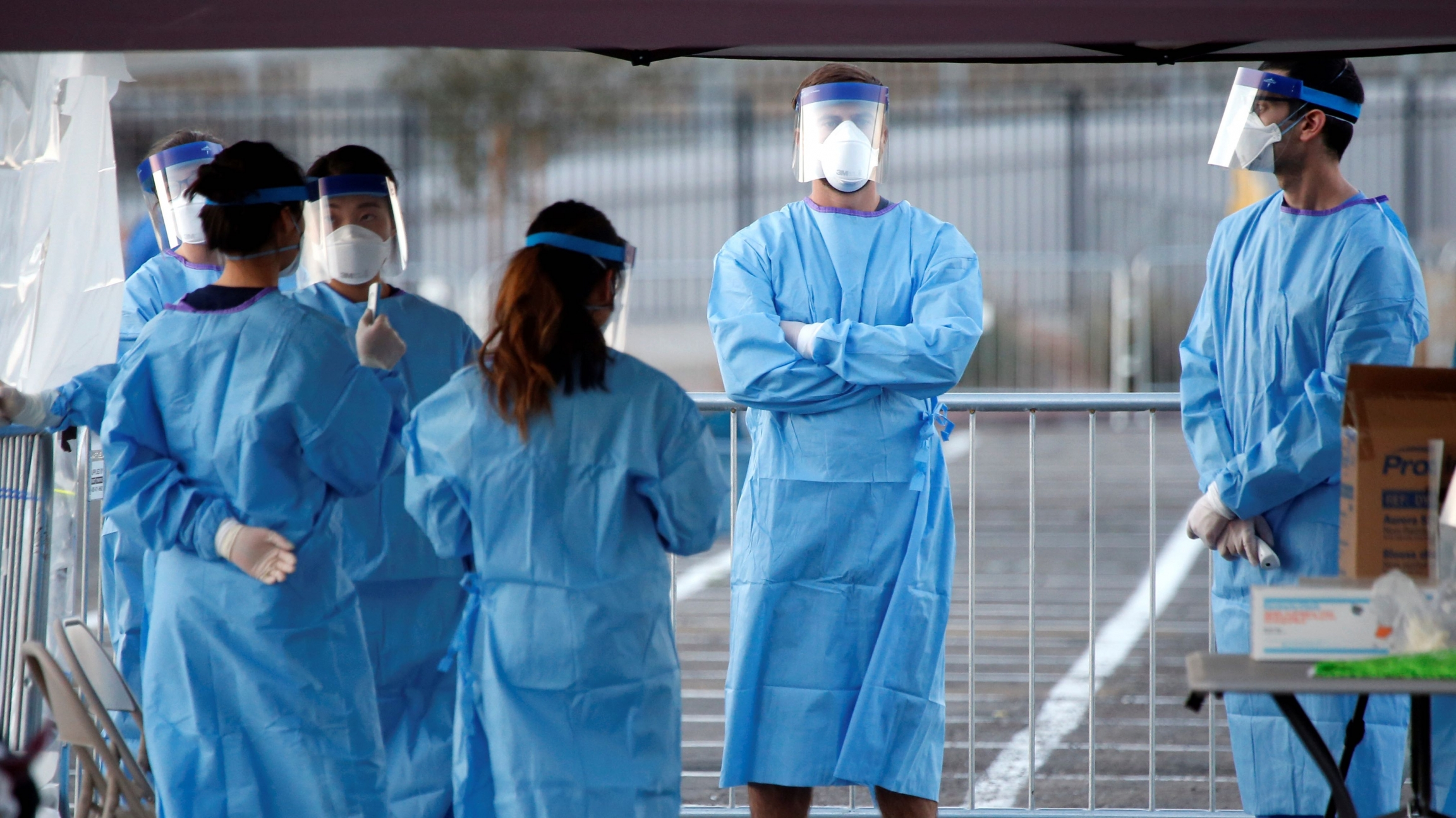 Medical students and physician assistants from Touro University Nevada wait to screen people in a temporary parking lot shelter at Cashman Center, with spaces marked for social distancing to help slow the spread of the coronavirus disease (COVID-19) in La