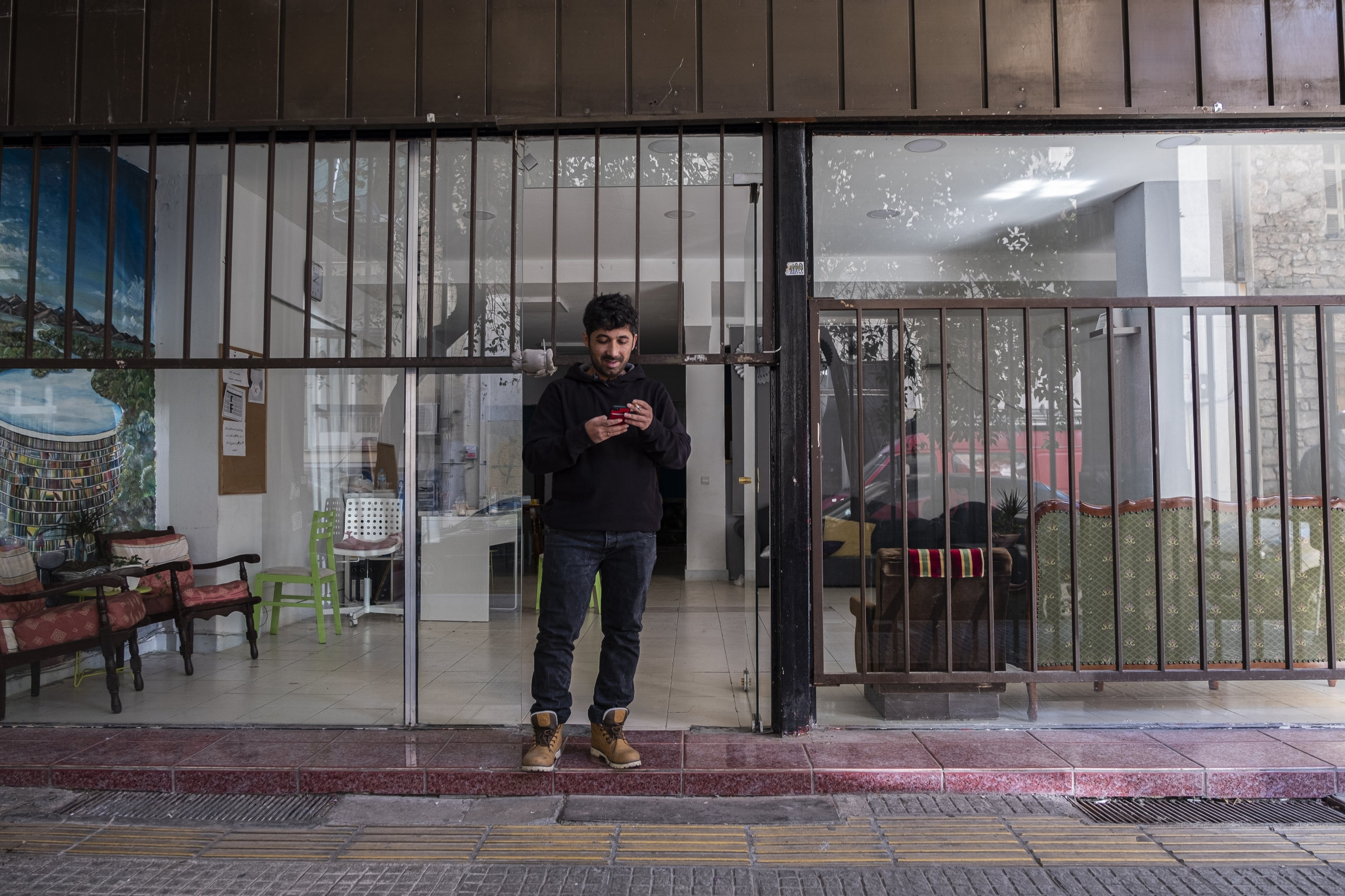 """Arash Hampay smokesin front of Cafe Patogh before the volunteers arrive to start packing and distributing the """"hope bags"""" in Athens, Greece."""