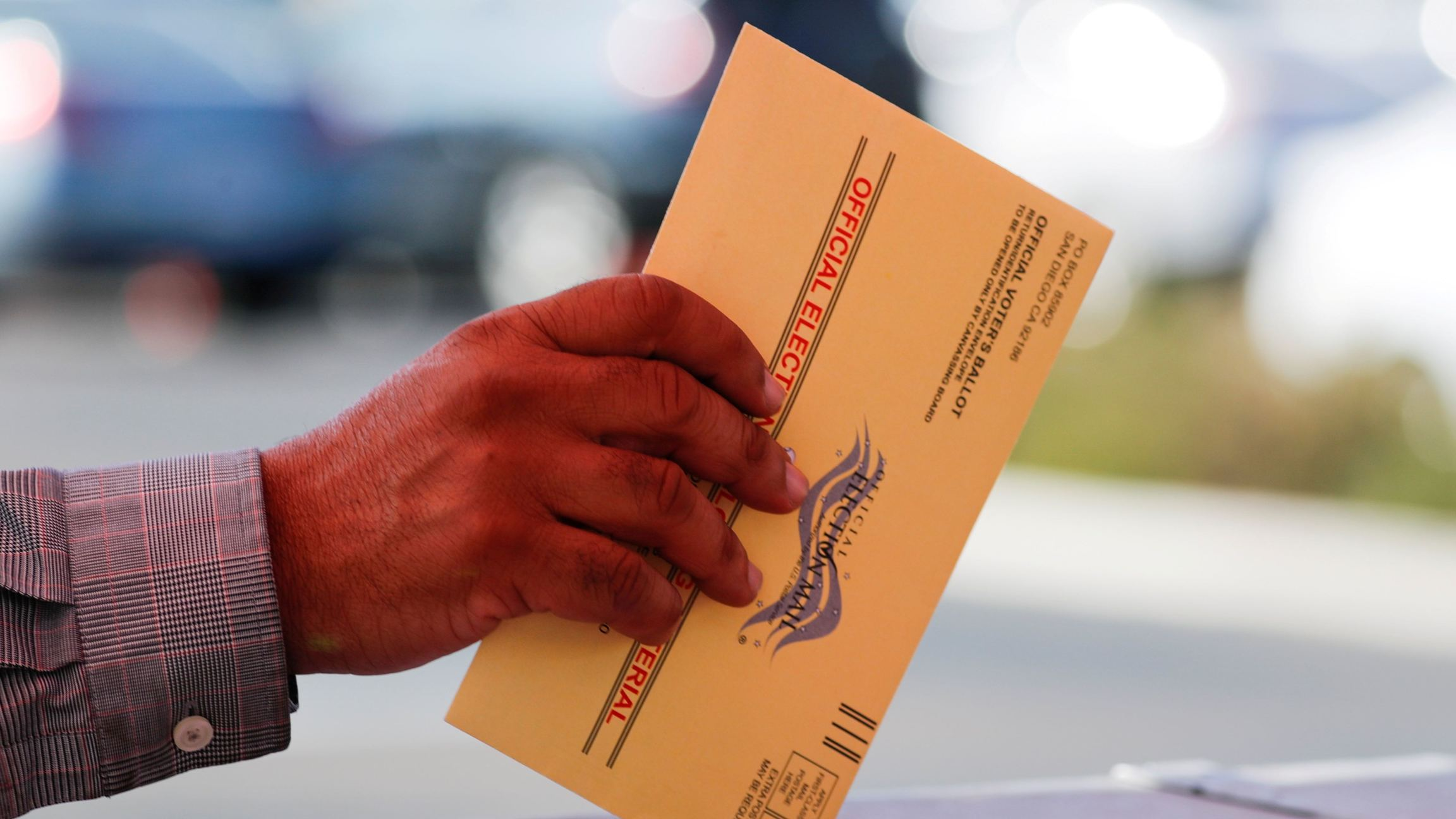 An election worker places a mail-in ballot into an election box at a drive-through drop off location at the Registrar of Voters in San Diego, Nov.5, 2018.