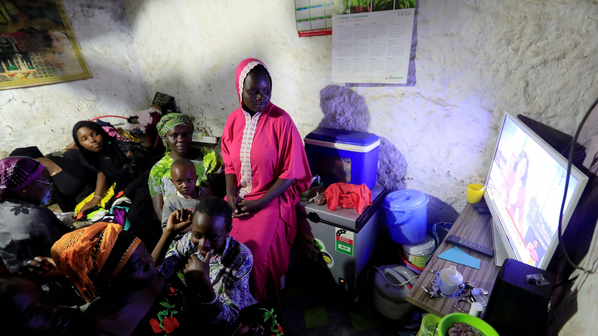 Residents watch a television at the beginning of a curfew which was ordered by the Kenya's President Uhuru Kenyatta to contain the spread of the coronavirus disease (COVID-19) inside a house within Kibera slums in Nairobi, Kenya, March 27, 2020.