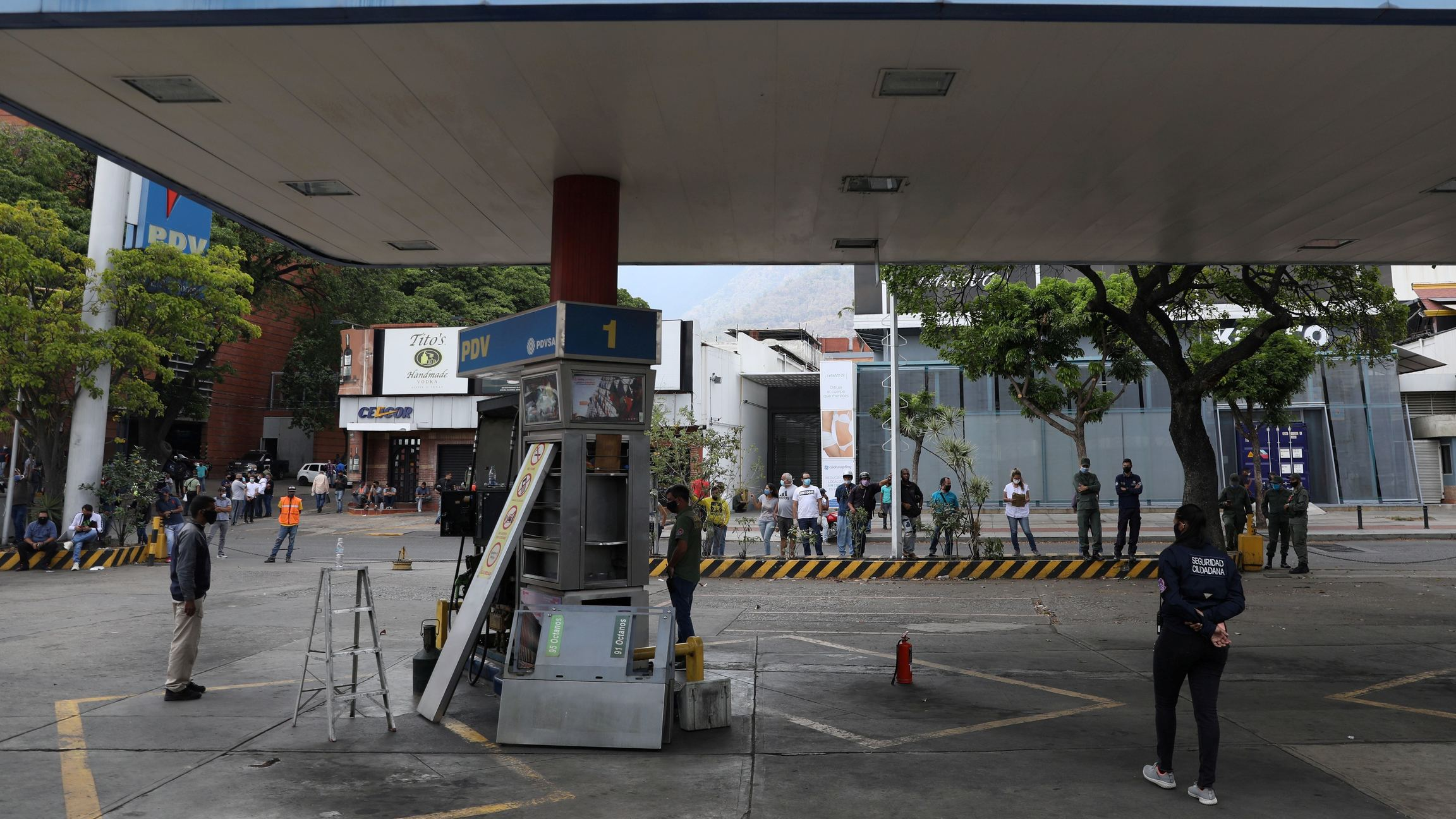Customers wait while a fuel dispenser machine is fixed at a gas station in Caracas, Venezuela, April 23, 2020.