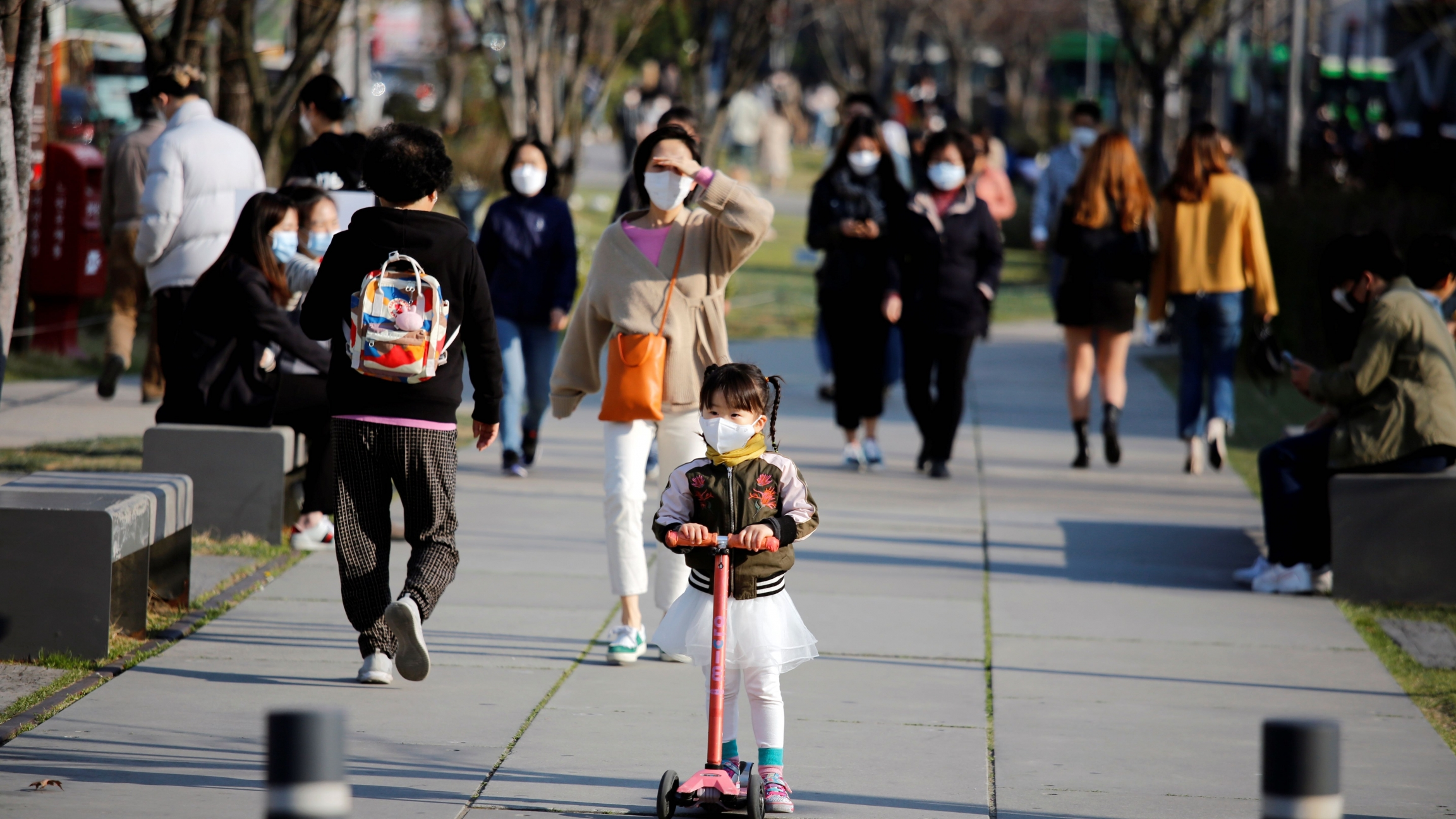 A girl wearing a protective face mask to prevent contracting the coronavirus disease (COVID-19) rides a toy kick scooter at a park in Seoul,SouthKorea, April 3, 2020.