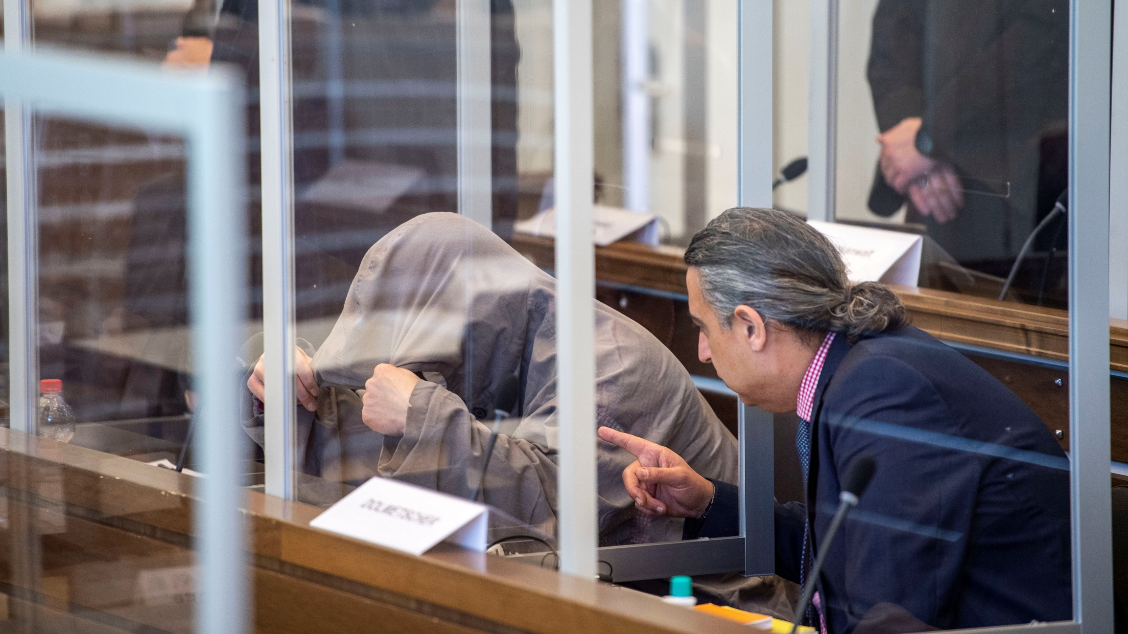 Syriandefendant Eyad A. hides himself under his hood prior to the first trial of suspected members ofSyrianPresident Bashar al-Assad's security services for crimes against humanity, in Koblenz,Germany, April 23, 2020.