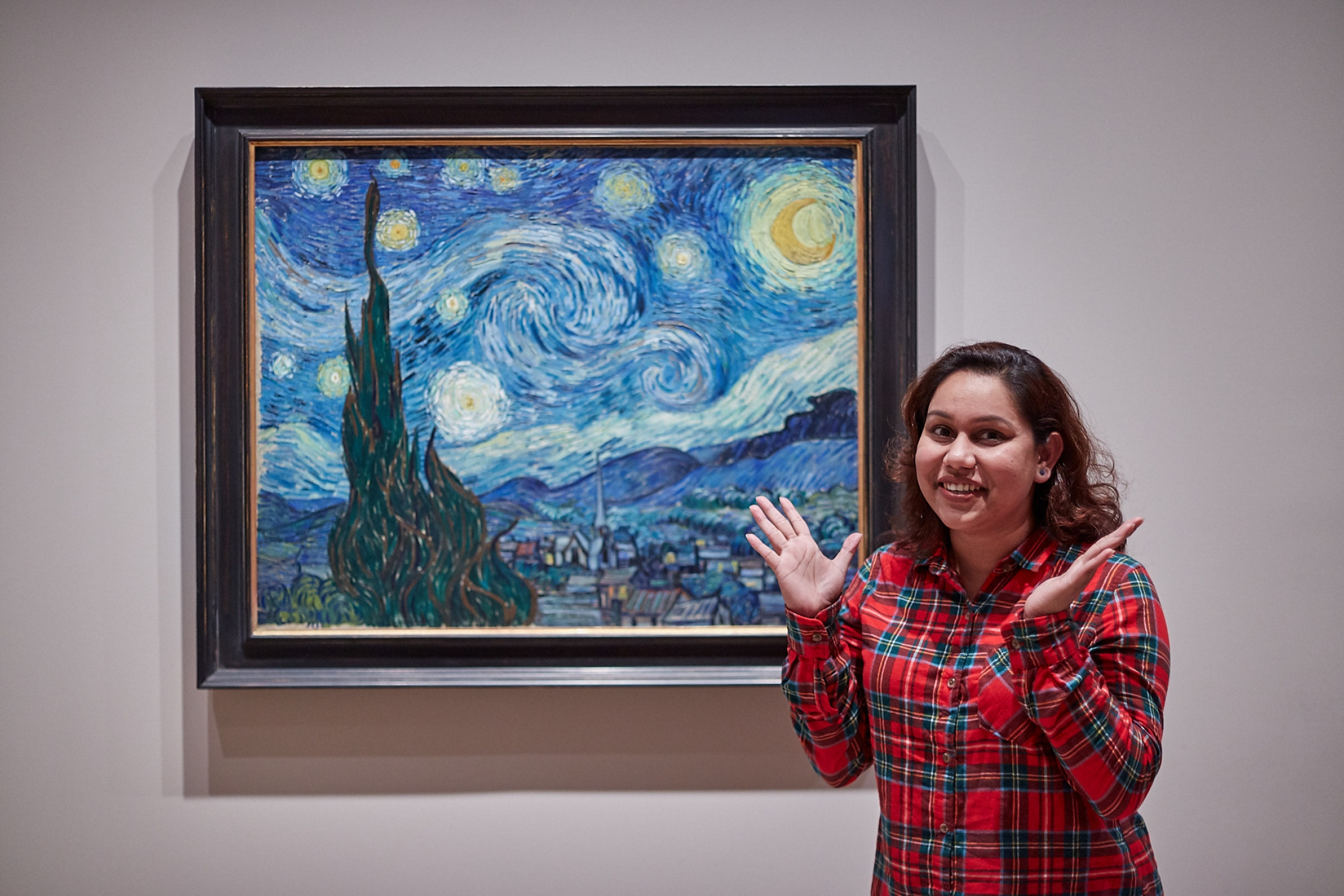 "A woman in a red-checkered shirt poses in front of Vincent van Gogh's famous painting, ""Starry Night."""