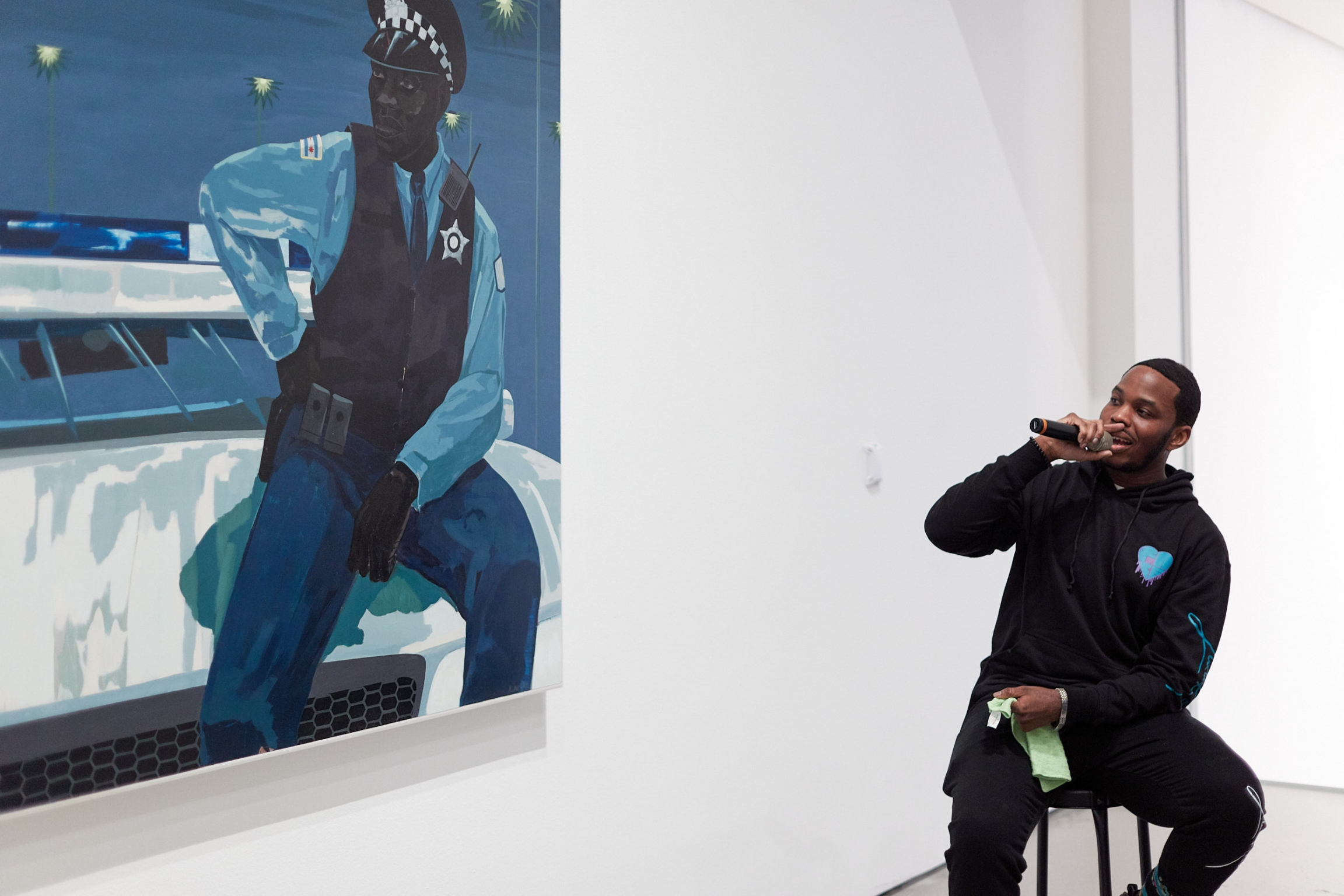 A man in a hoodie sits on a barstool holding a microphone as he looks to a blue-hued painting of a policeman.