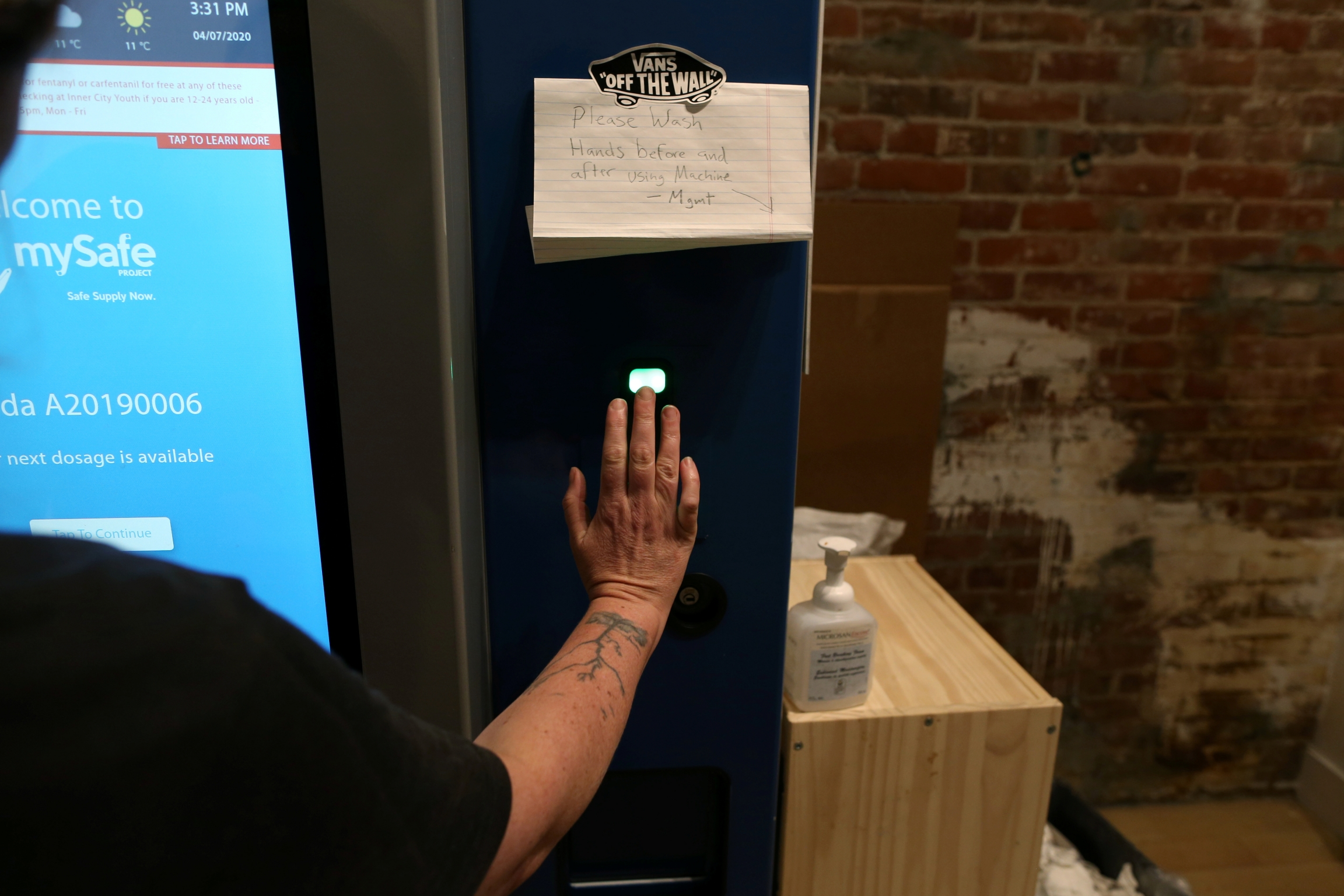 "A woman demonstrates how the mySafe narcotic dispensing machine uses a palm-print ID at the Overdose Prevention Society as the local health unit has begun prescribing a ""safe supply"" of narcotic alternatives to combat overdoses due to poisonous additives"