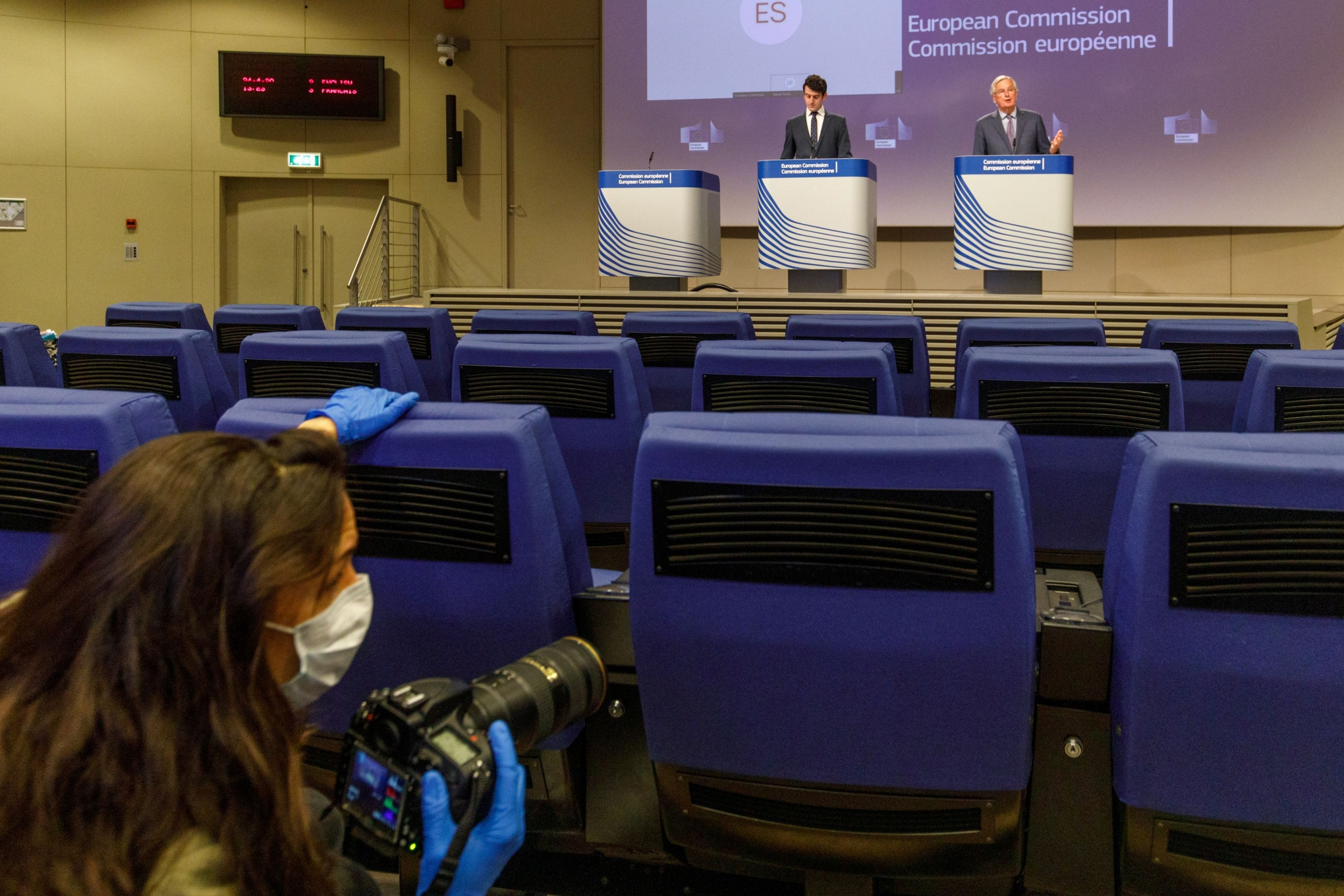 EU's Brexit negotiator Michel Barnier gives a news conference after Brexit negotiations, as a photographer wearing a mass passes by in the foreground, in Brussels, Belgium, on April 24, 2020.