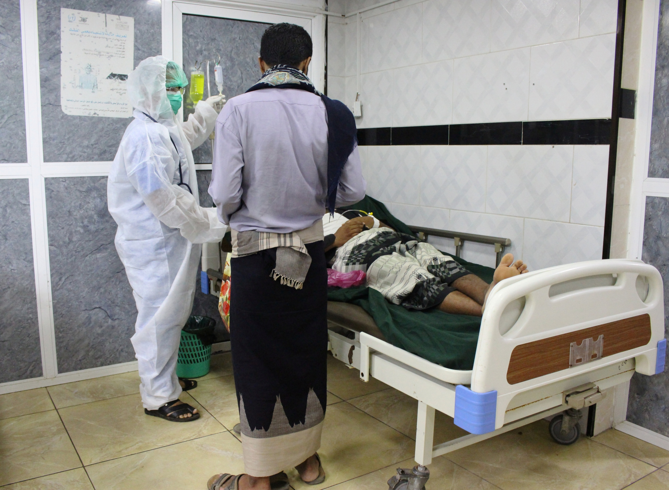 A medic wearing a protective suit attends to a patient at the emergency ward of a hospital amid concerns about the spread of the coronavirus disease, COVID-19, in Aden, Yemen