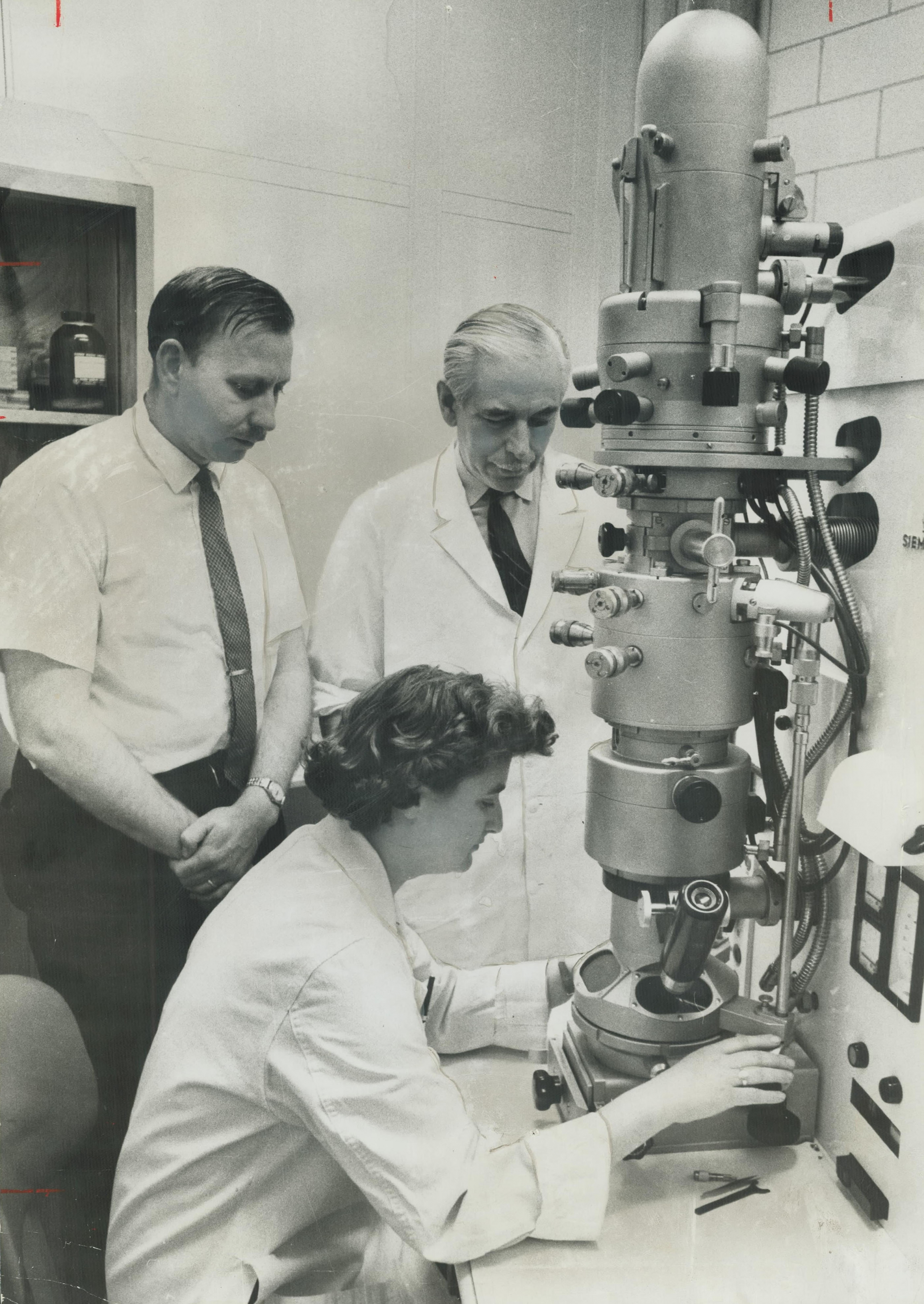 June Almeida, Scotish virologist looks into an electron microscope.