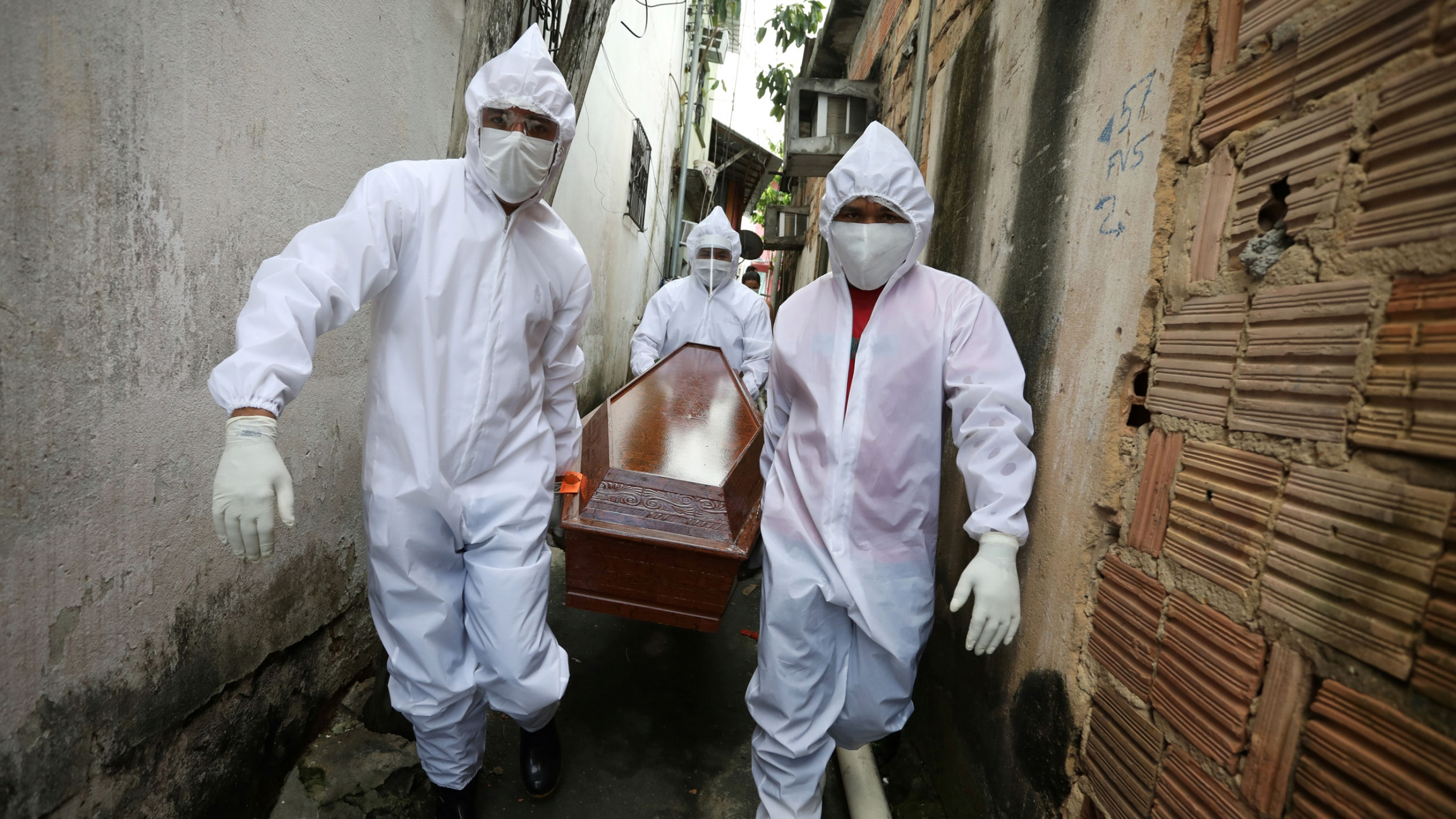Three workers are shown wearing white medical protective clothing and masks while carrying a wooden coffing in a small alley.