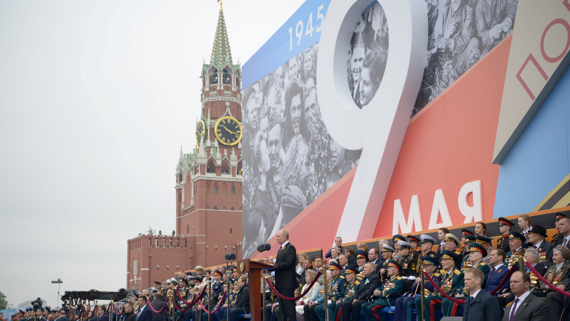 Putin stands at a podium in front of a crowd and signage for May 9