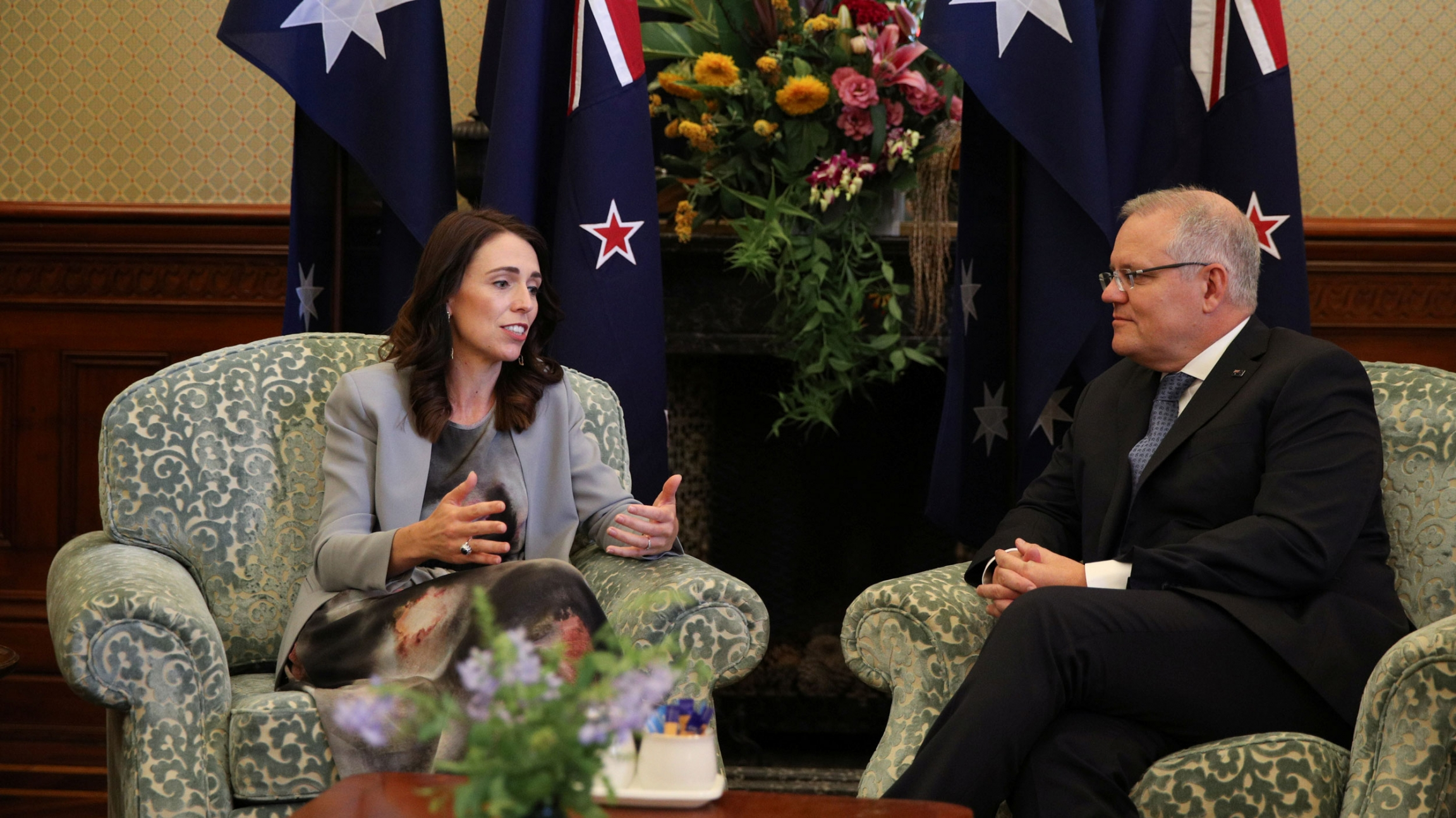 A woman and a man sit in chairs in front of the New Zealand and Australian flags