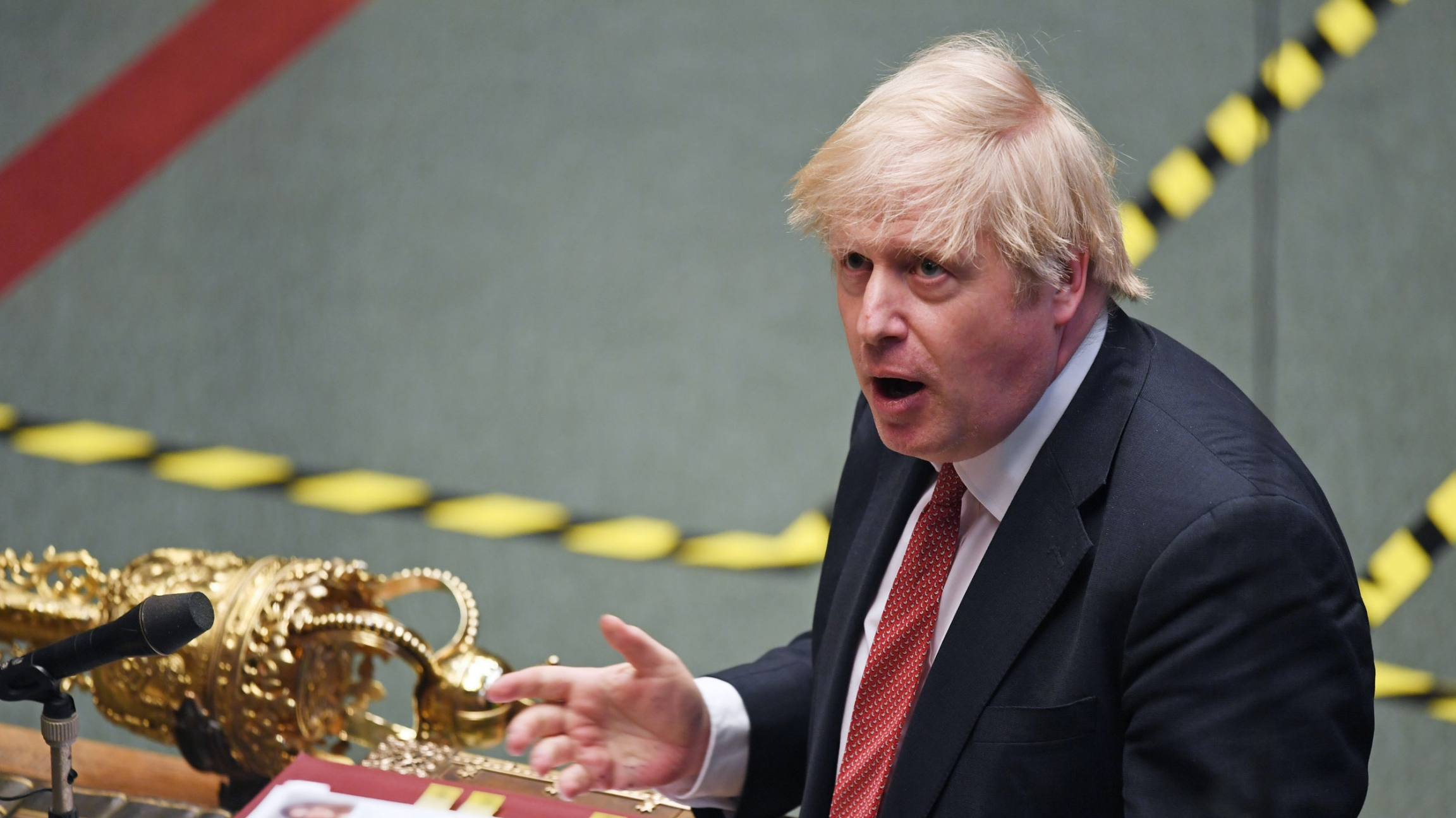 Britain's Prime Minister Boris Johnson is shown in a photograph from above standing at a podium with his hand outstretched.