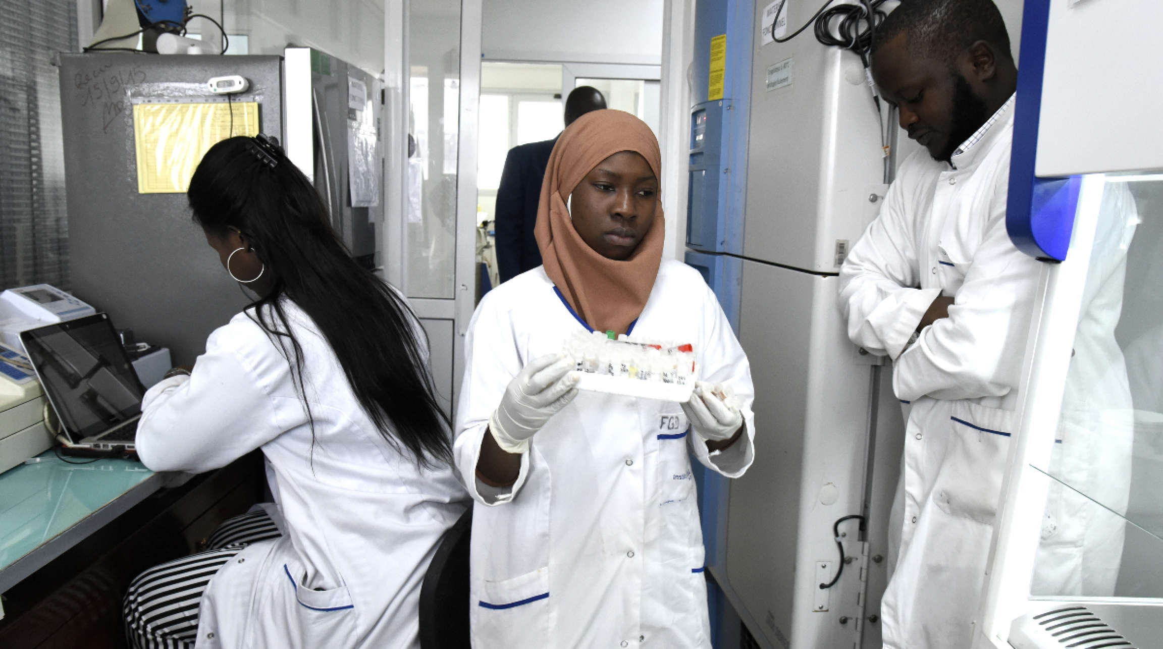A woman in a white robe carries some lab material inside lab in Senegal.