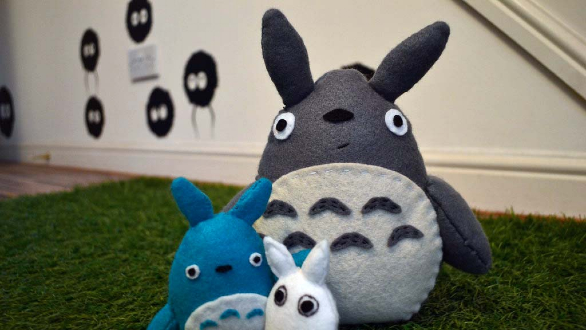 "A stuffed animal Totoro and other characters from the 1988 Japanese anime film ""My Neighbor Totoro."""