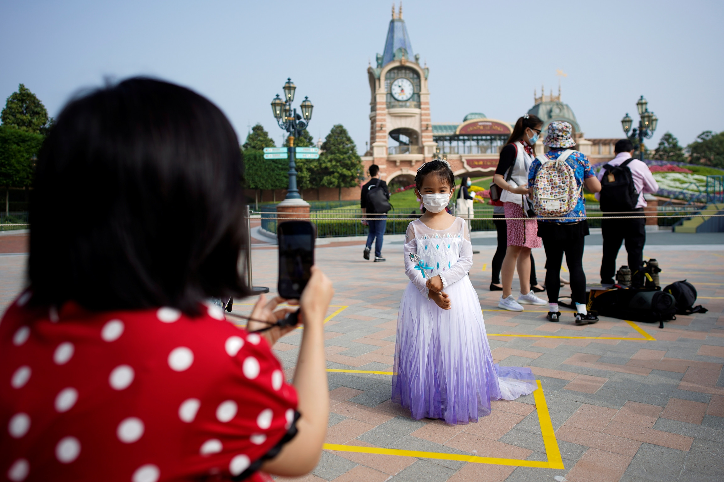 A mother photographs her child wearing a face mask and a princess gown at Disneyland in Shanghai.
