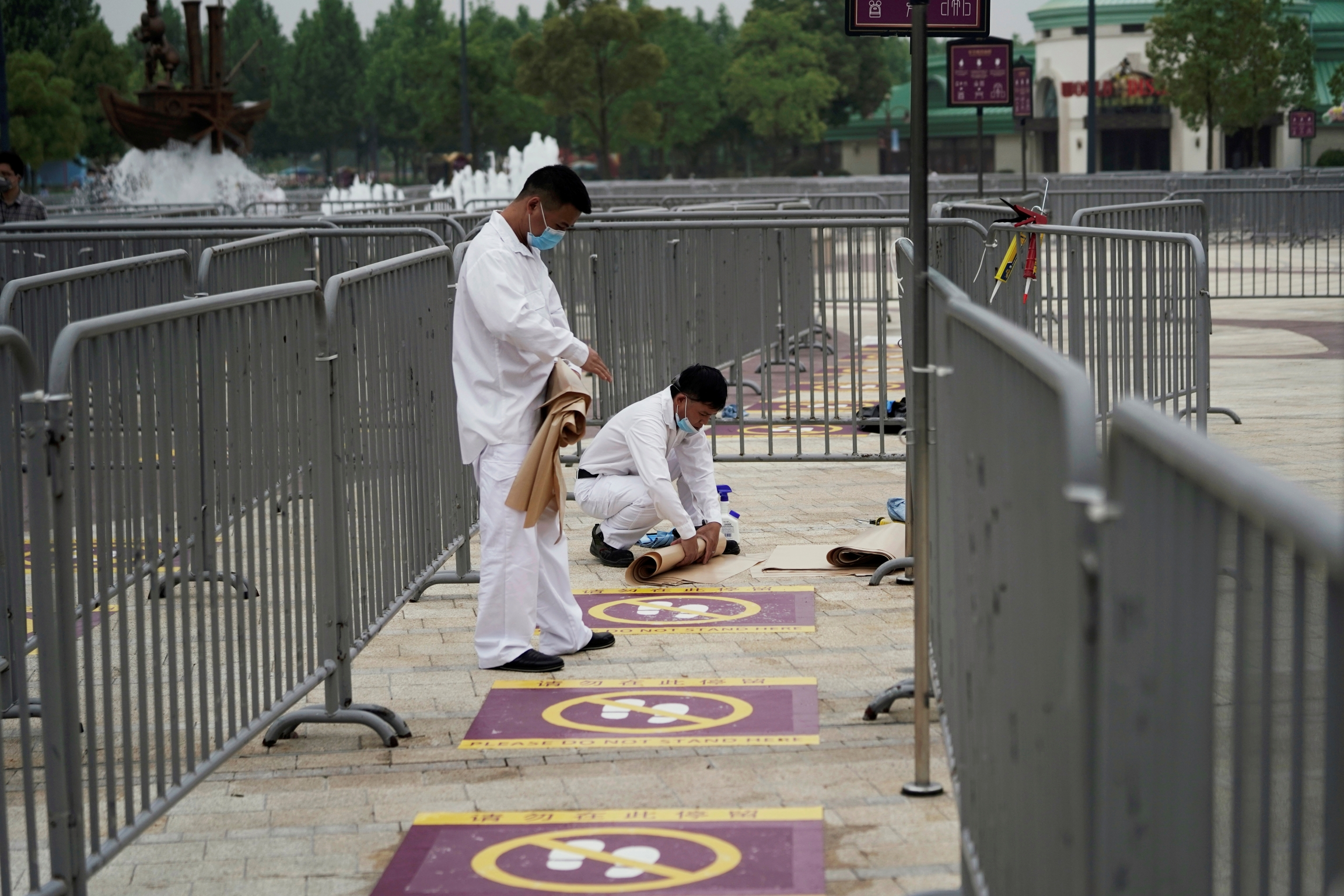 Workers wearing face masks paint social distance markers on the ground at Shangahi Disneyland