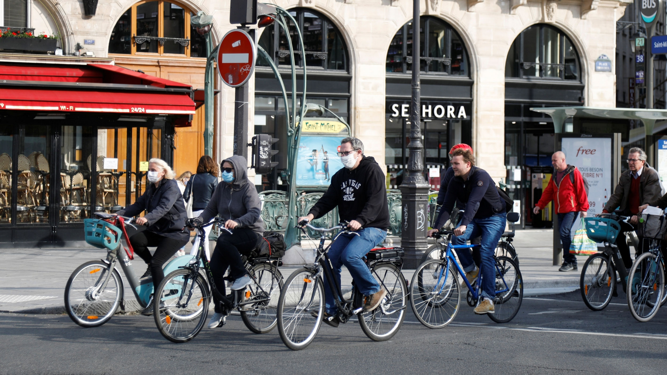 A group of several people are shown riding bicycles in the streets and wearing protective face masks.