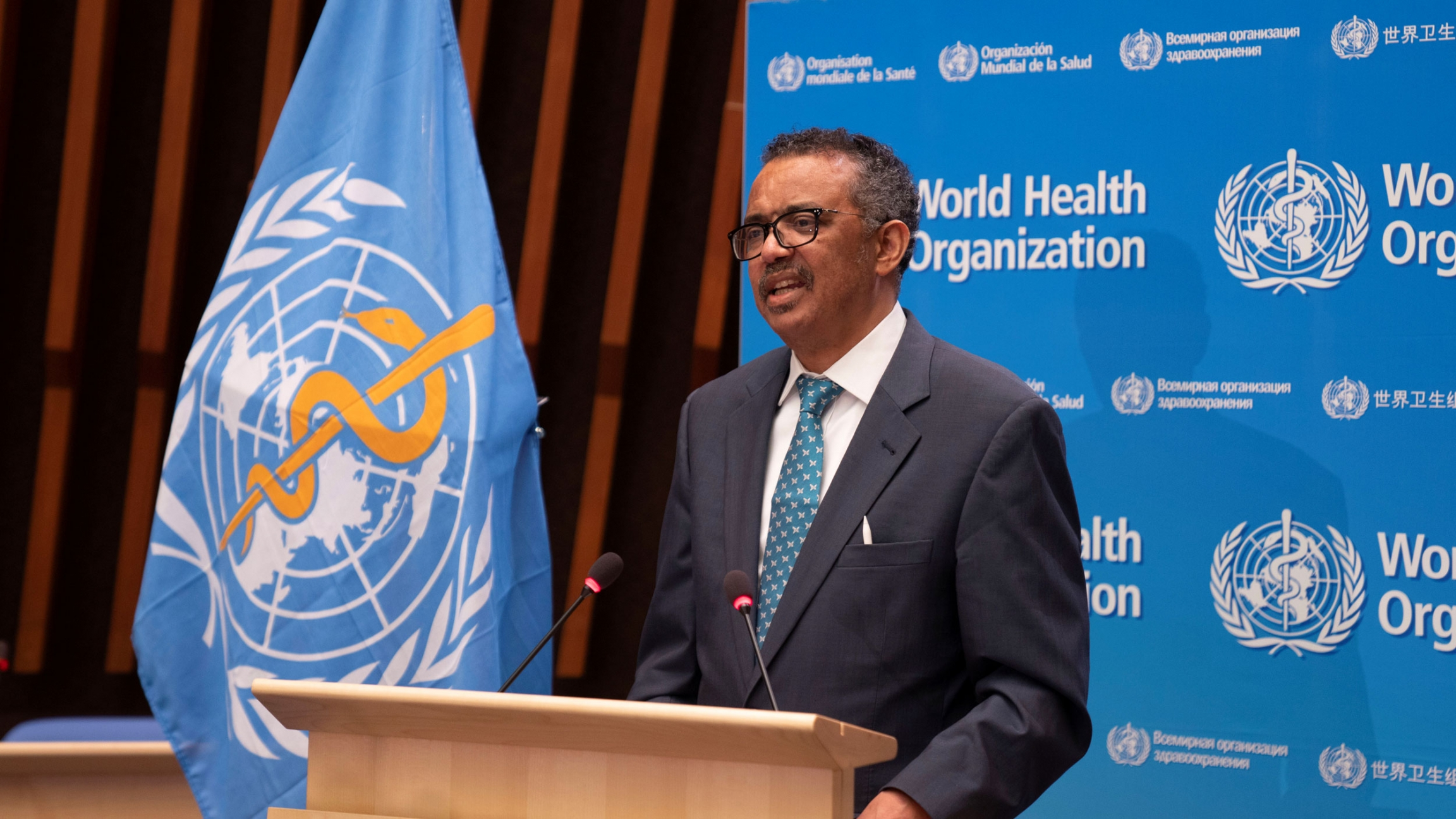 Tedros Adhanom Ghebreyesus is shown standing at a wooden podium with the blue WHO flag next to him.