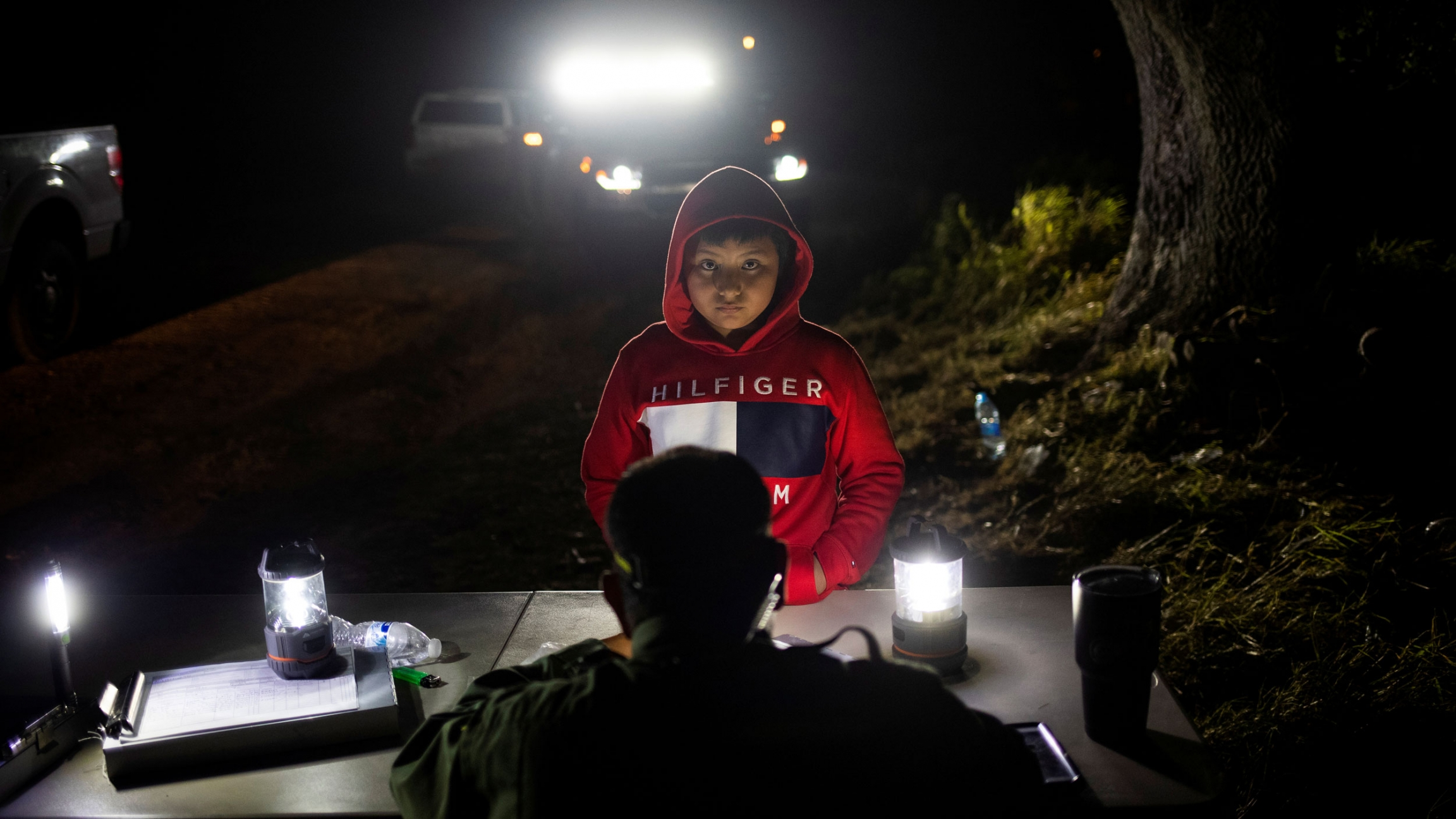 A young boy is shown wearing a red hooded sweatshirt and standing at a border patrol table.