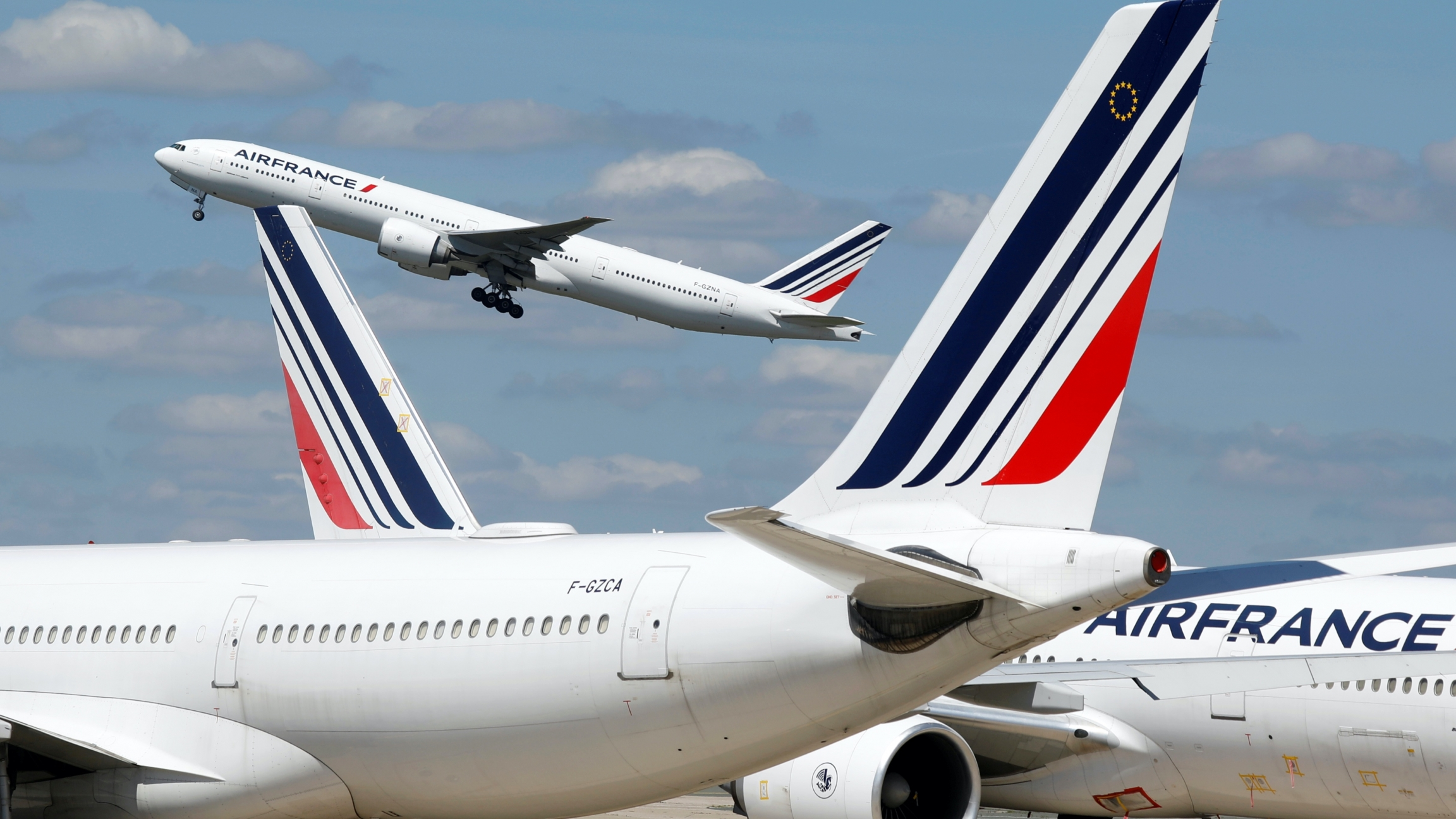 Three Air France white airplanes at the airport, one in the air
