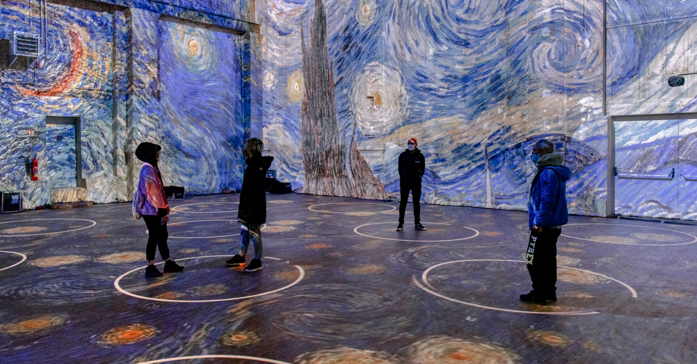 "A photo mock up of Van Gogh art projected in a space with people standing in ""social distance circles."""