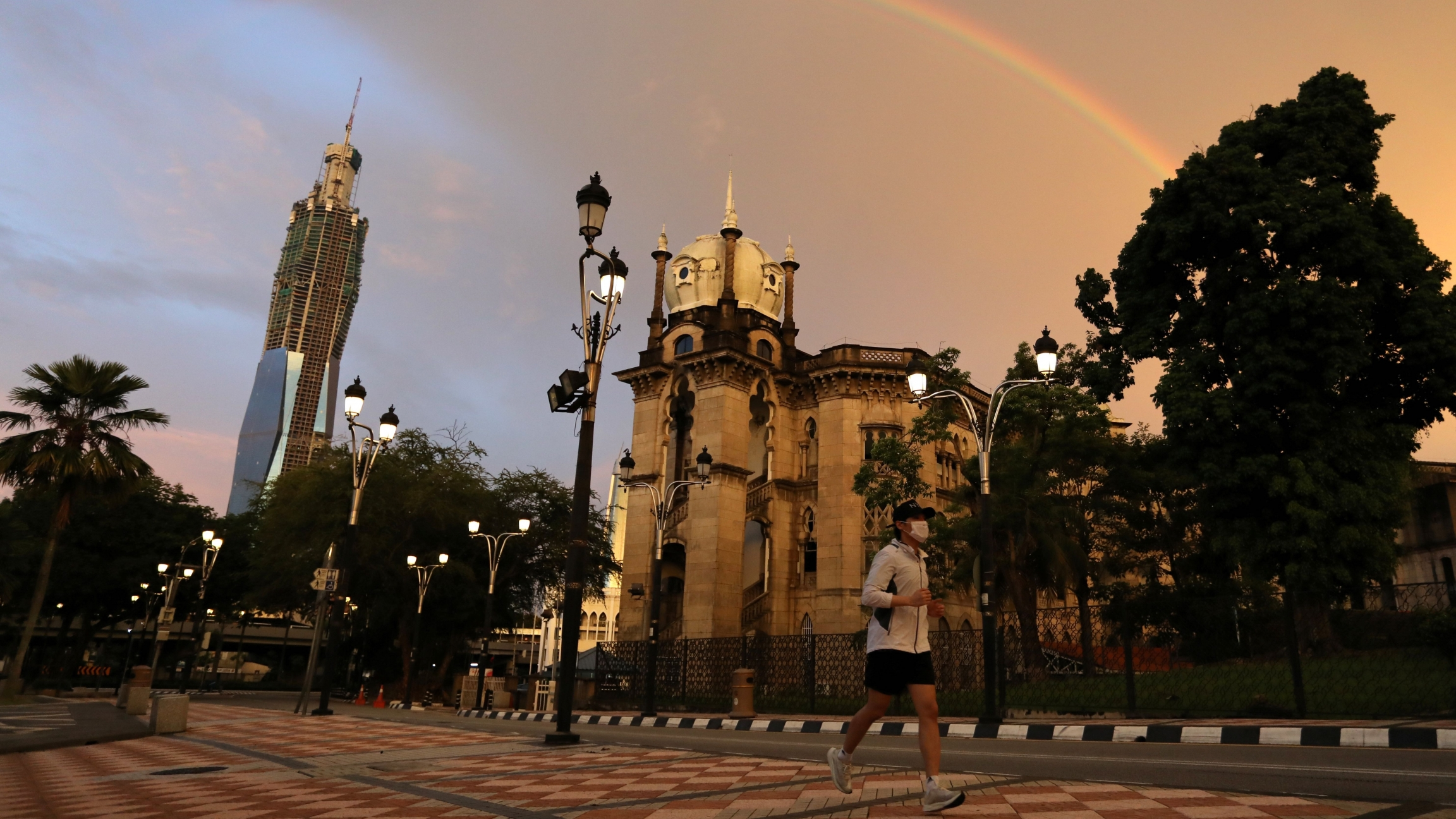 A man wearing protective face mask jogs under a rainbow as Malaysia reopens a majority of businesses, after a movement control order was imposed to fight the outbreak of the coronavirus disease (COVID-19), in Kuala Lumpur, Malaysia May 4, 2020.
