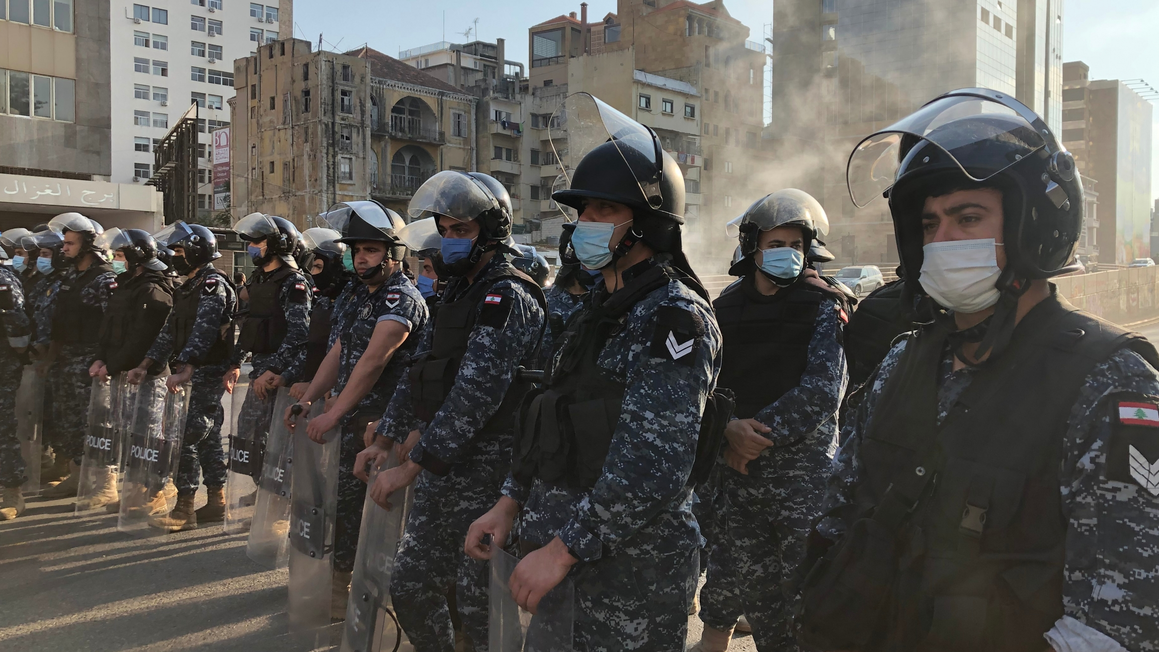 People in military uniform wear face masks while they form a line on a Beirut street during protest.