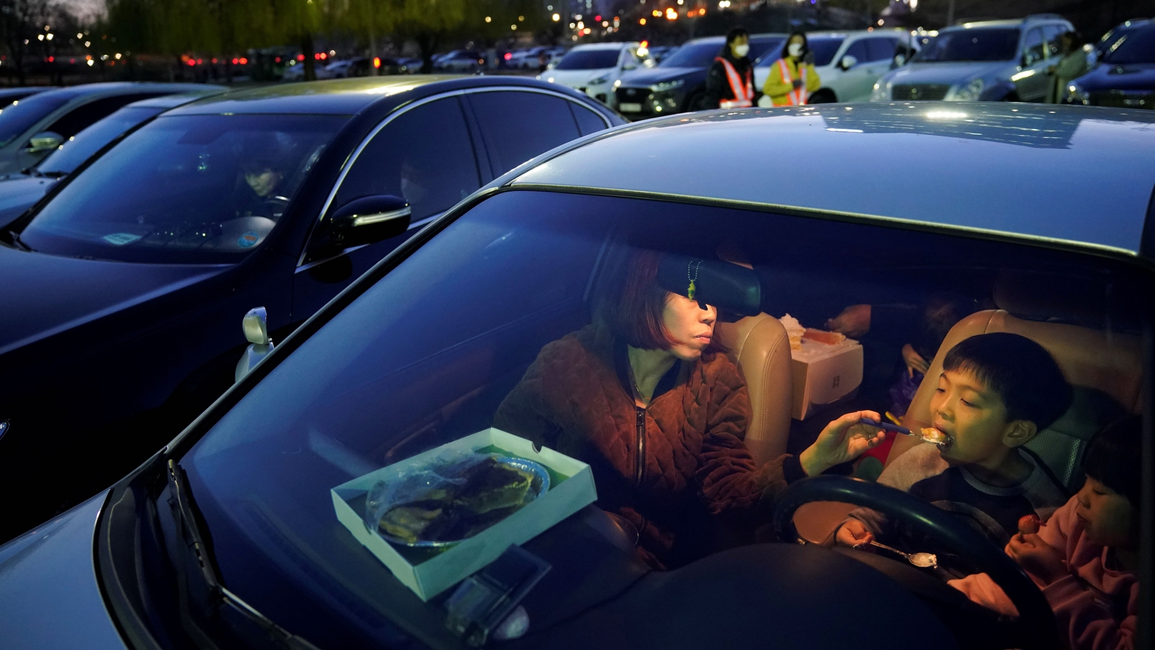 A woman feeds her child as they prepare to watch a movie from their car at a temporary made drive-in theater while keeping social distancing following the outbreak of the coronavirus disease (COVID-19), in Seoul, South Korea, March 27, 2020.