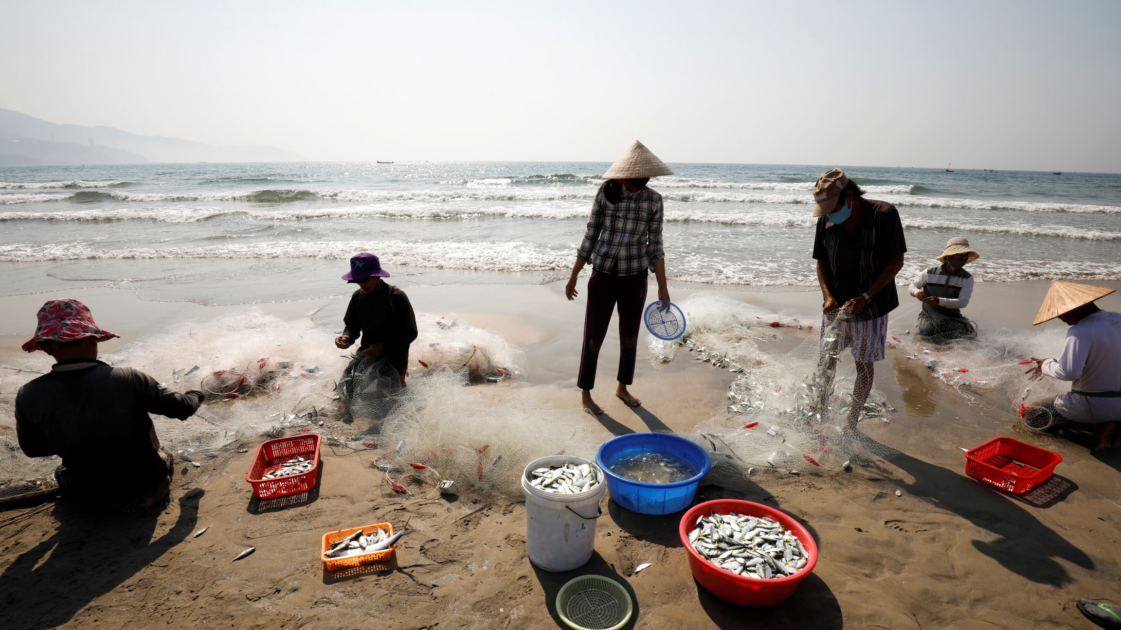 People wearing protective masks collect fishes on a beach during the coronavirus disease (COVID-19) outbreak in Da Nang city, Vietnam, May 6, 2020.