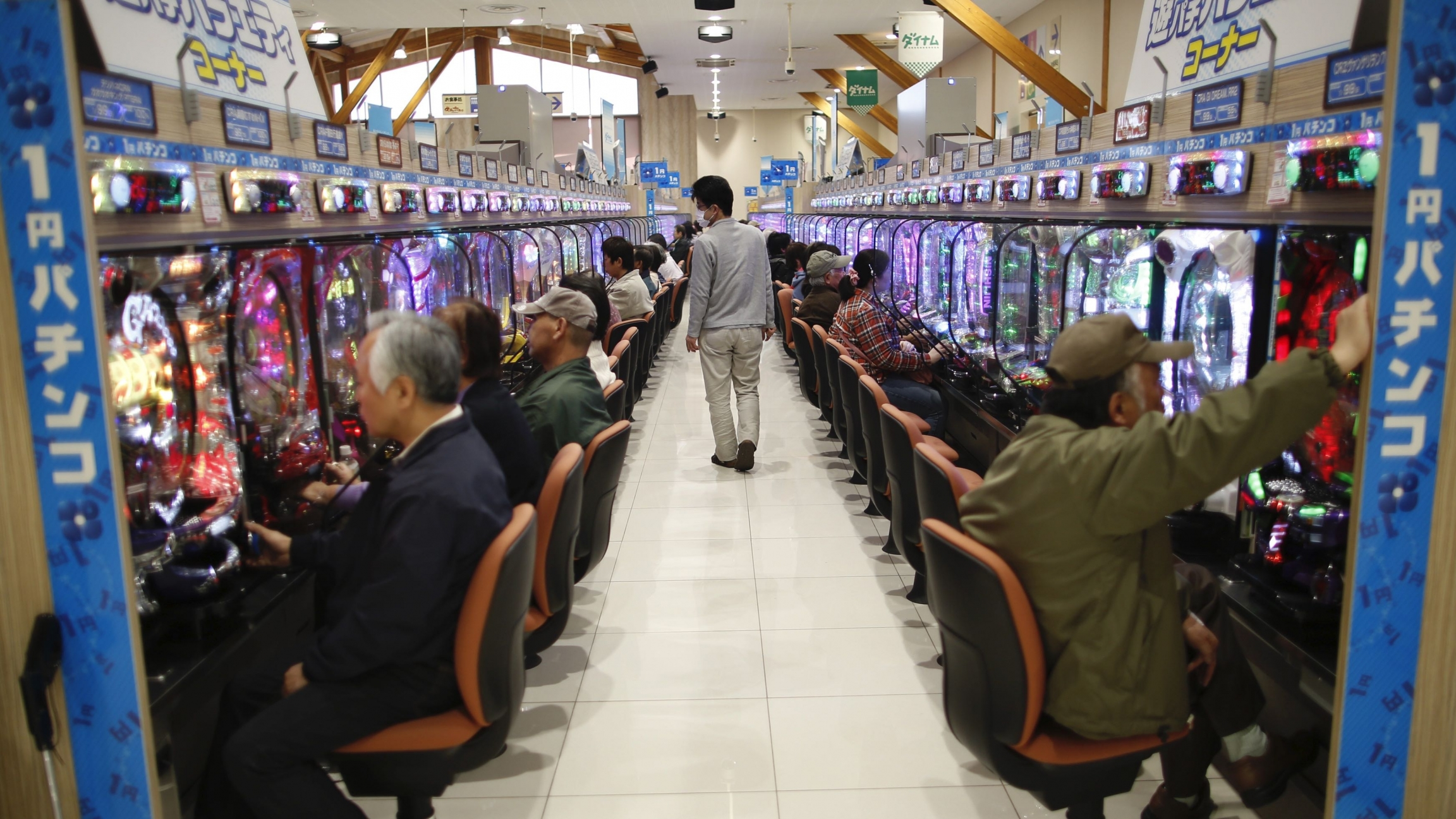 Visitors play Pachinko, a Japanese form of legal gambling, at Dynam Japan Holdings Co.'s Pachinko parlour in Koga, north of Tokyo, April 7, 2014.