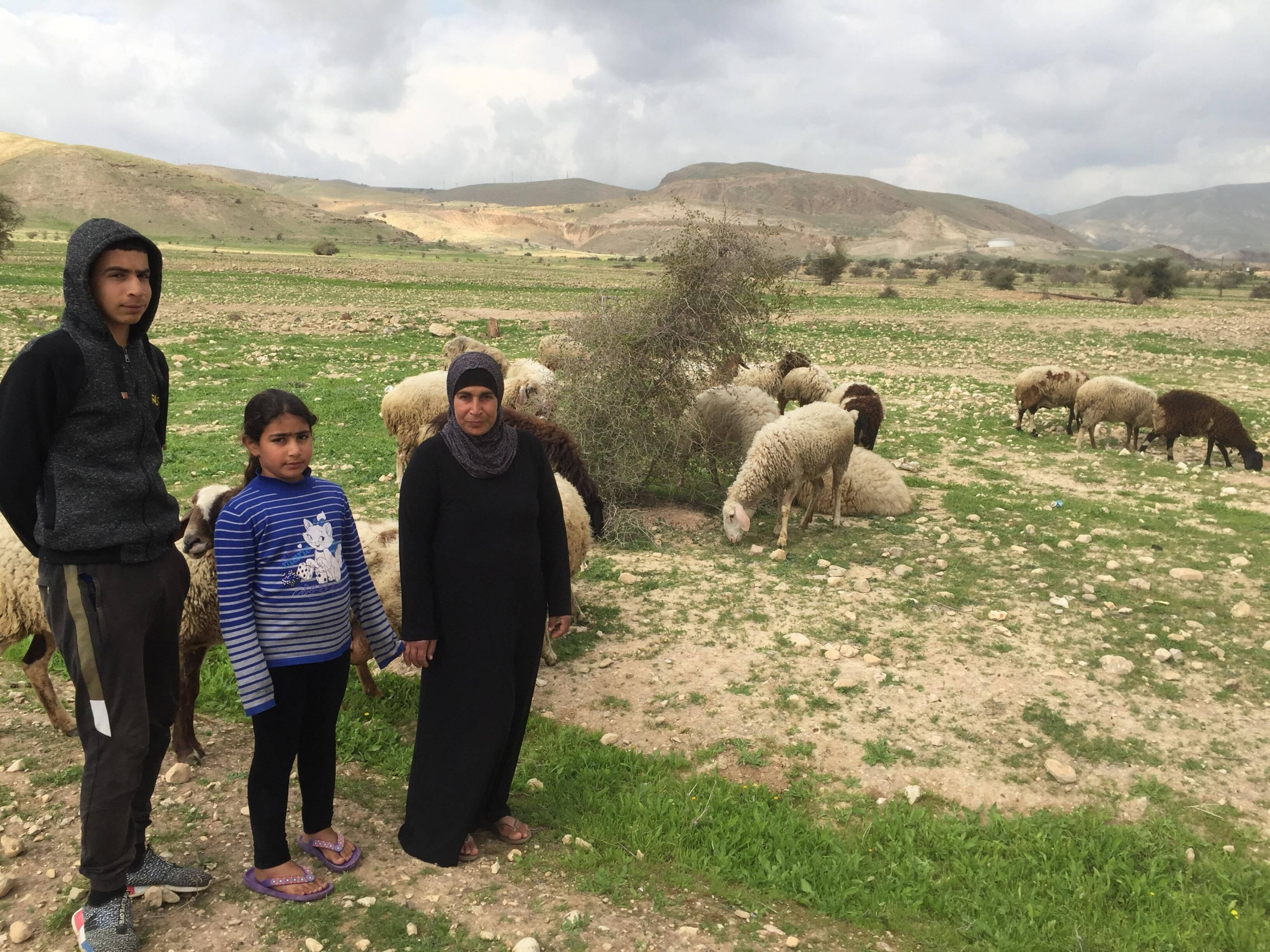 Iyad Ebbayat, left, his younger sister, and his mother, Noor Ebbayat with their sheep in the Palestinian village of Fasayil.
