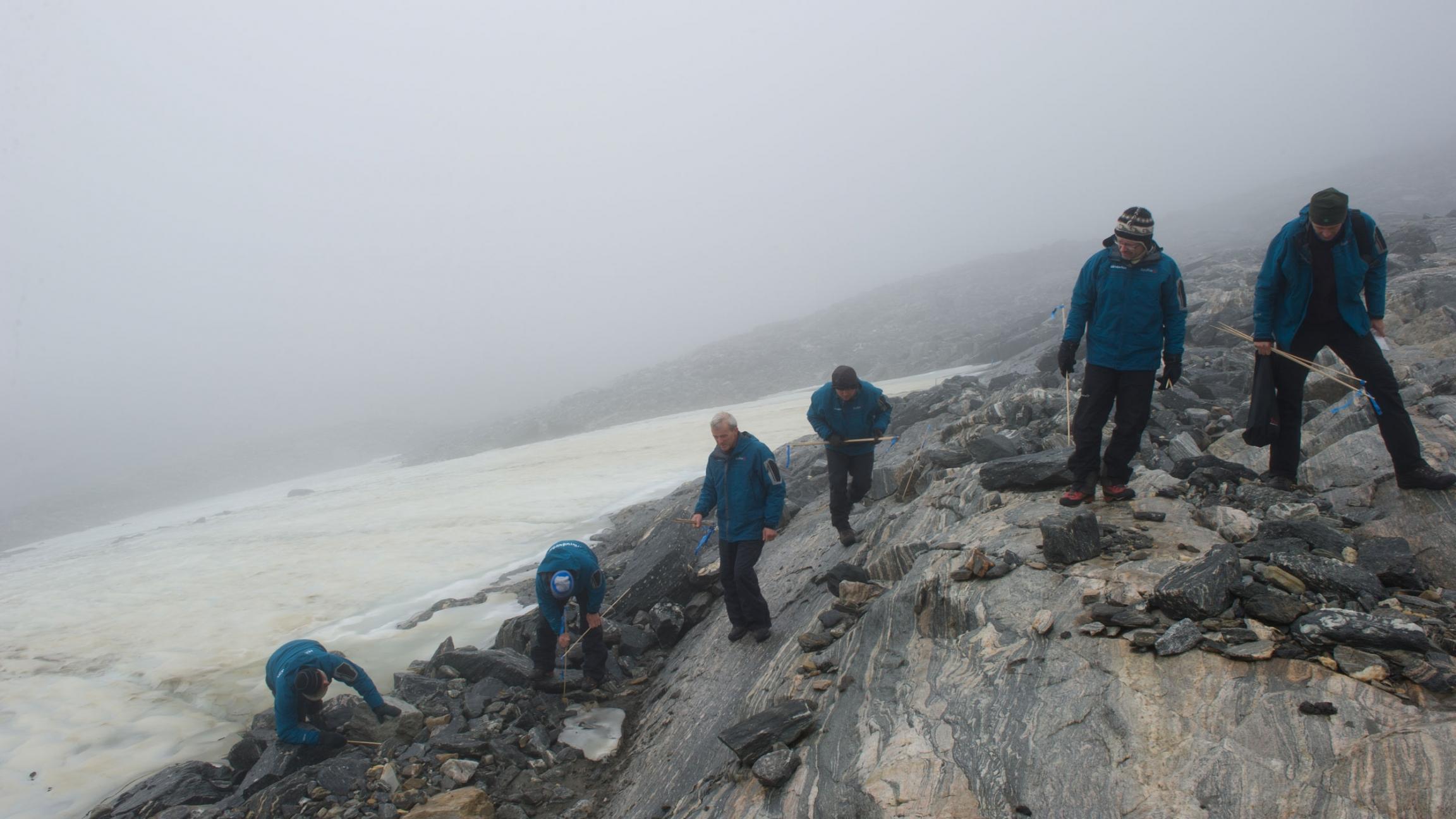 Men walk along an ice patch
