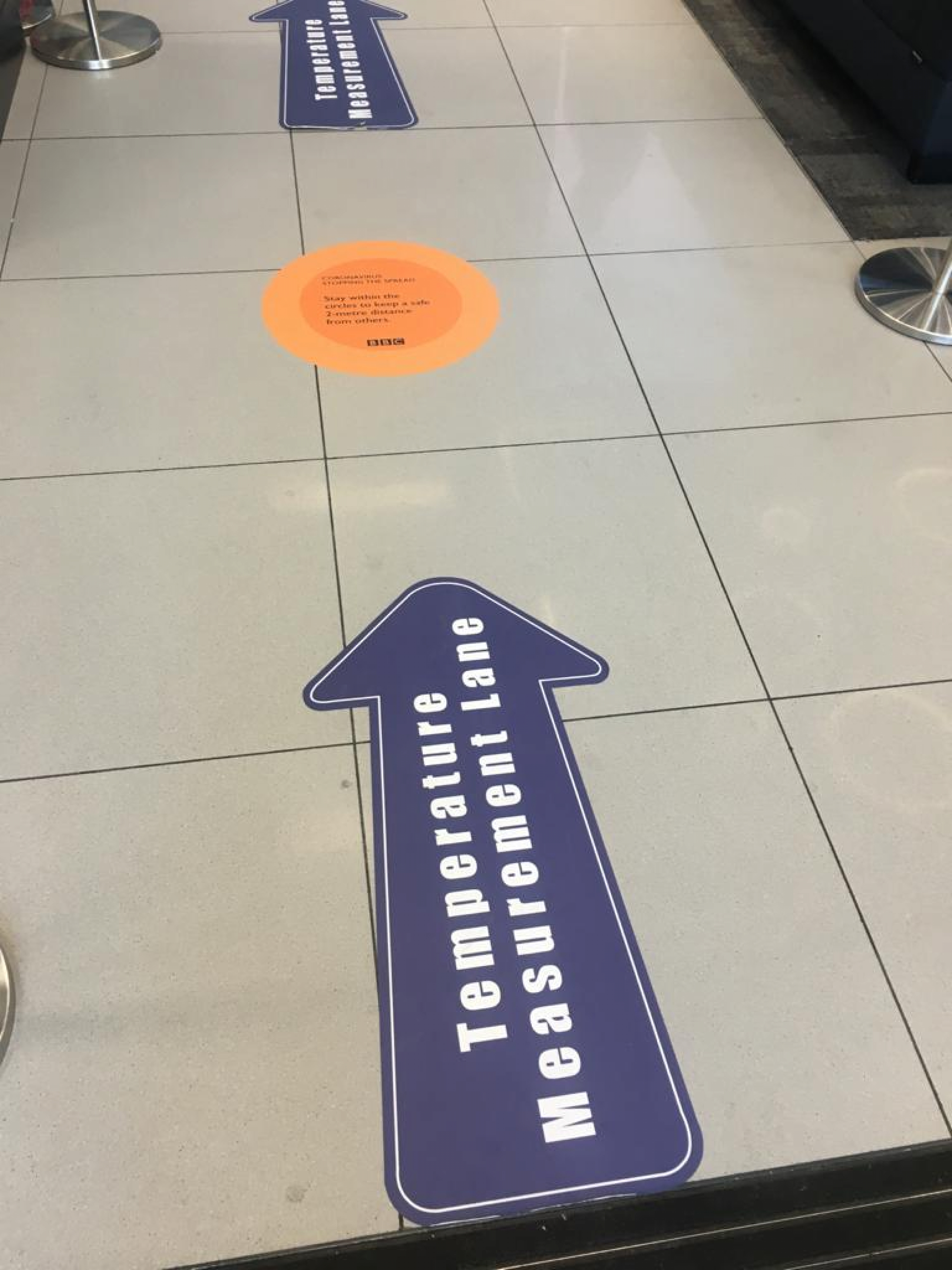 Signs on the floor at the BBC direct people to the thermal scanners.