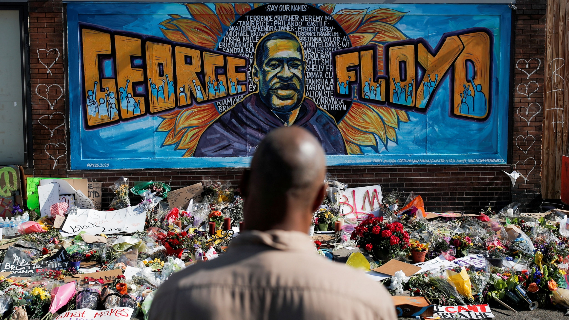 A black man stands in front of a mural honoring George Floyd and other black Americans killed by law enforcement
