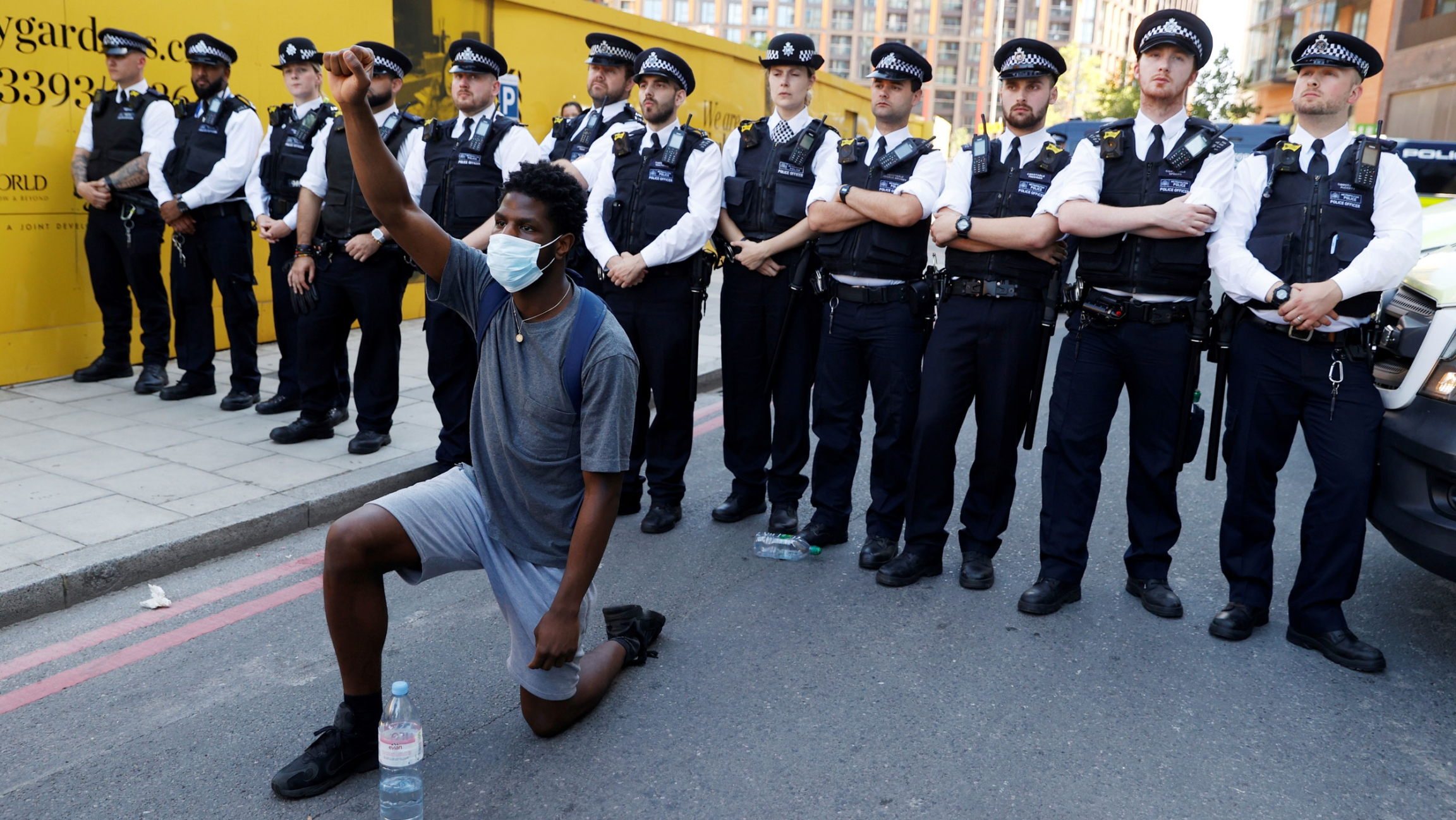 A man is shown kneeling and with his right fist raised with a line of police standing behind him.