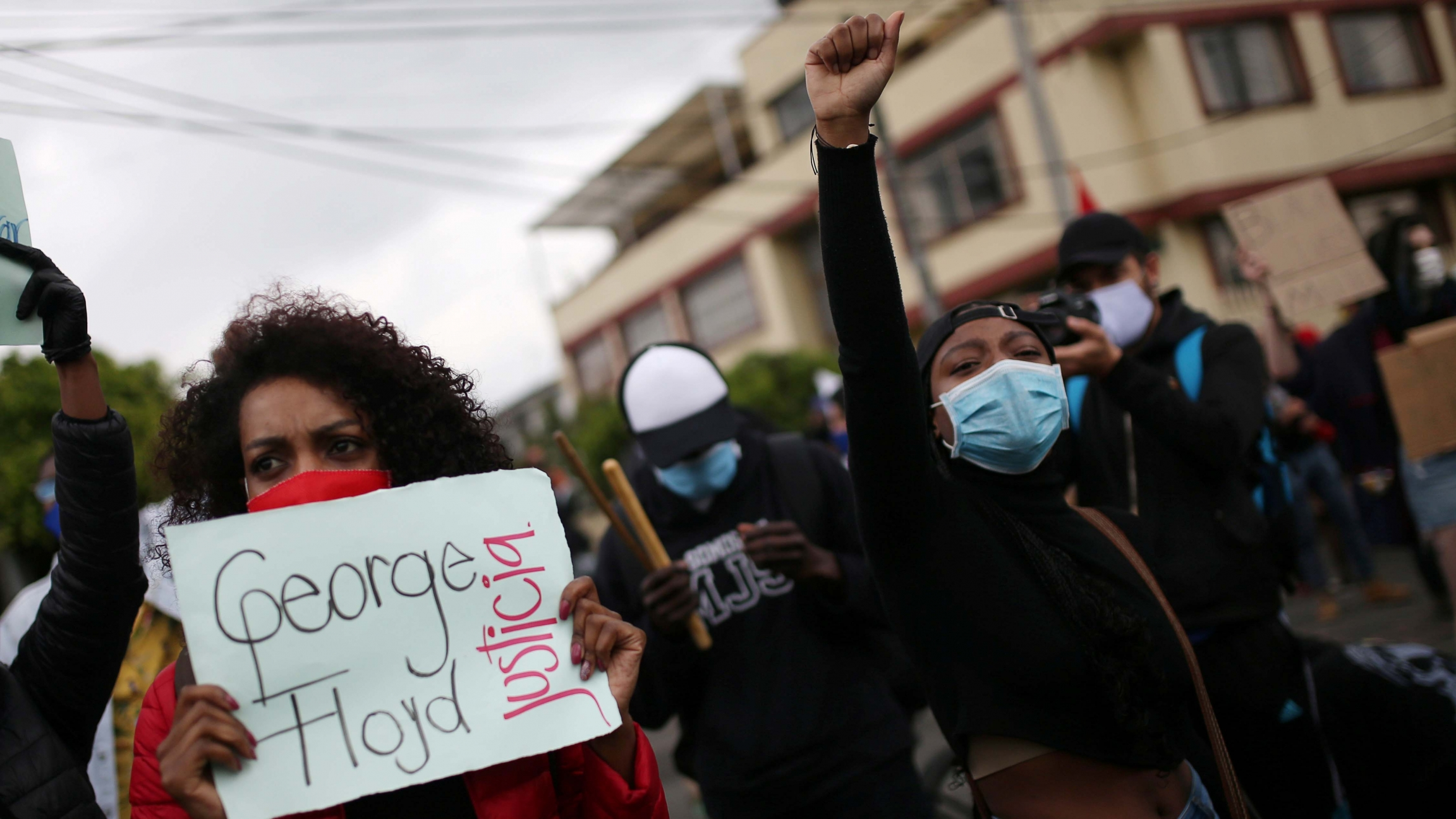 "A demonstrator holds a sign that reads ""George Floyd, justice"" during a protest against the death in Minneapolis police custody of George Floyd and the arrival of US troops in Colombian territory, in Bogotá, Colombia, on June 3, 2020."
