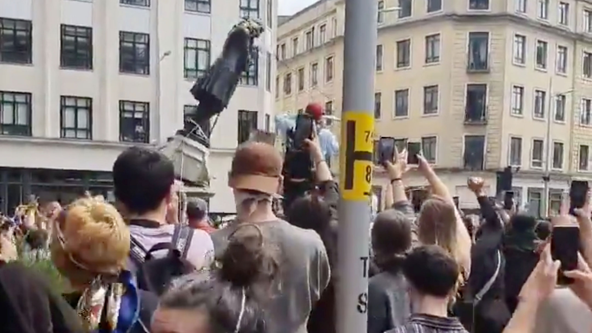A large group of protesters are shown pulling down the metal statue of Edward Colston.