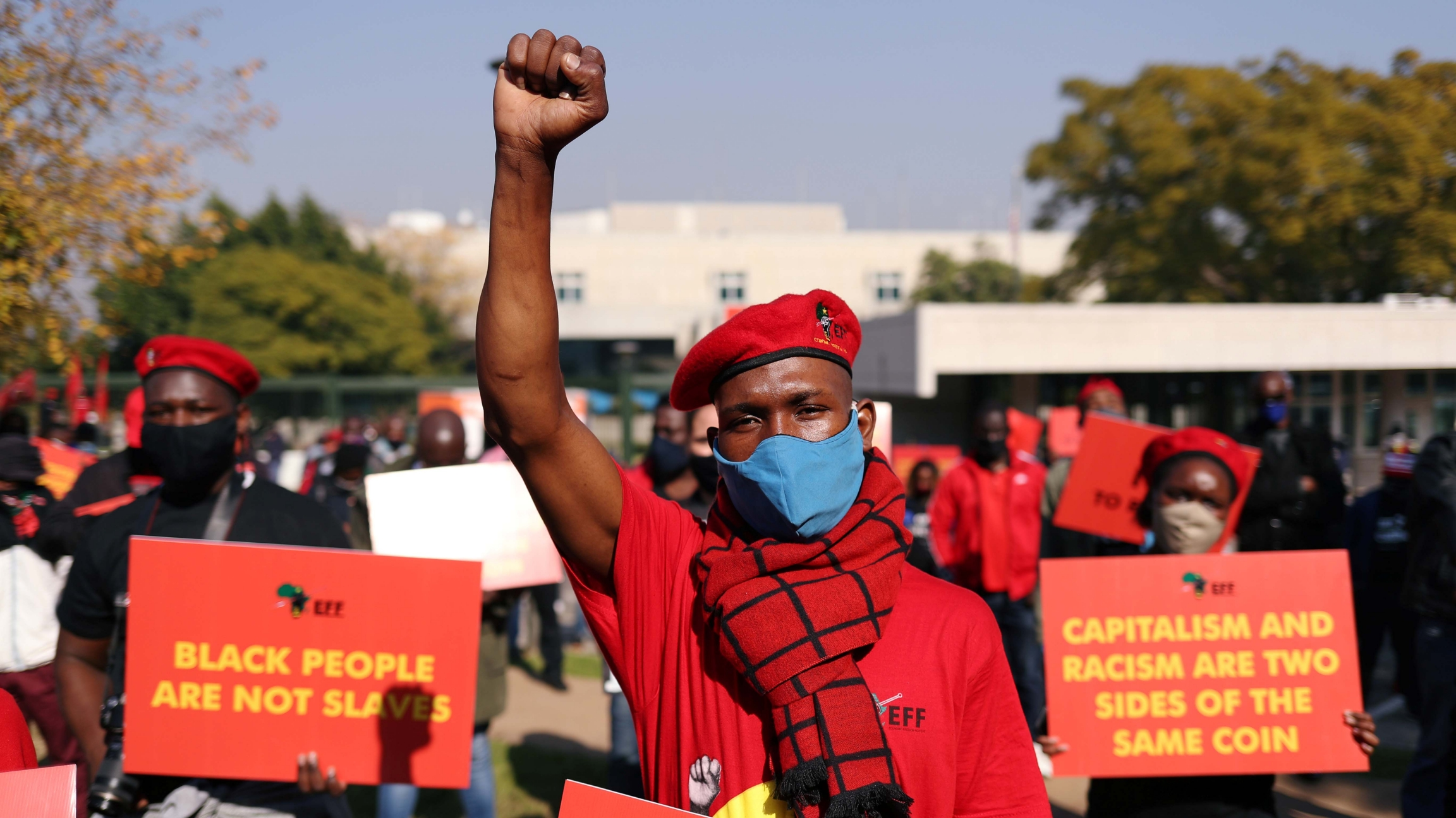 A member of South Africa's opposition party, the Economic Freedom Fighters (EFF), wears a red shirt and chants outside the US embassy in Pretoria, South Africa, on June 8, 2020.