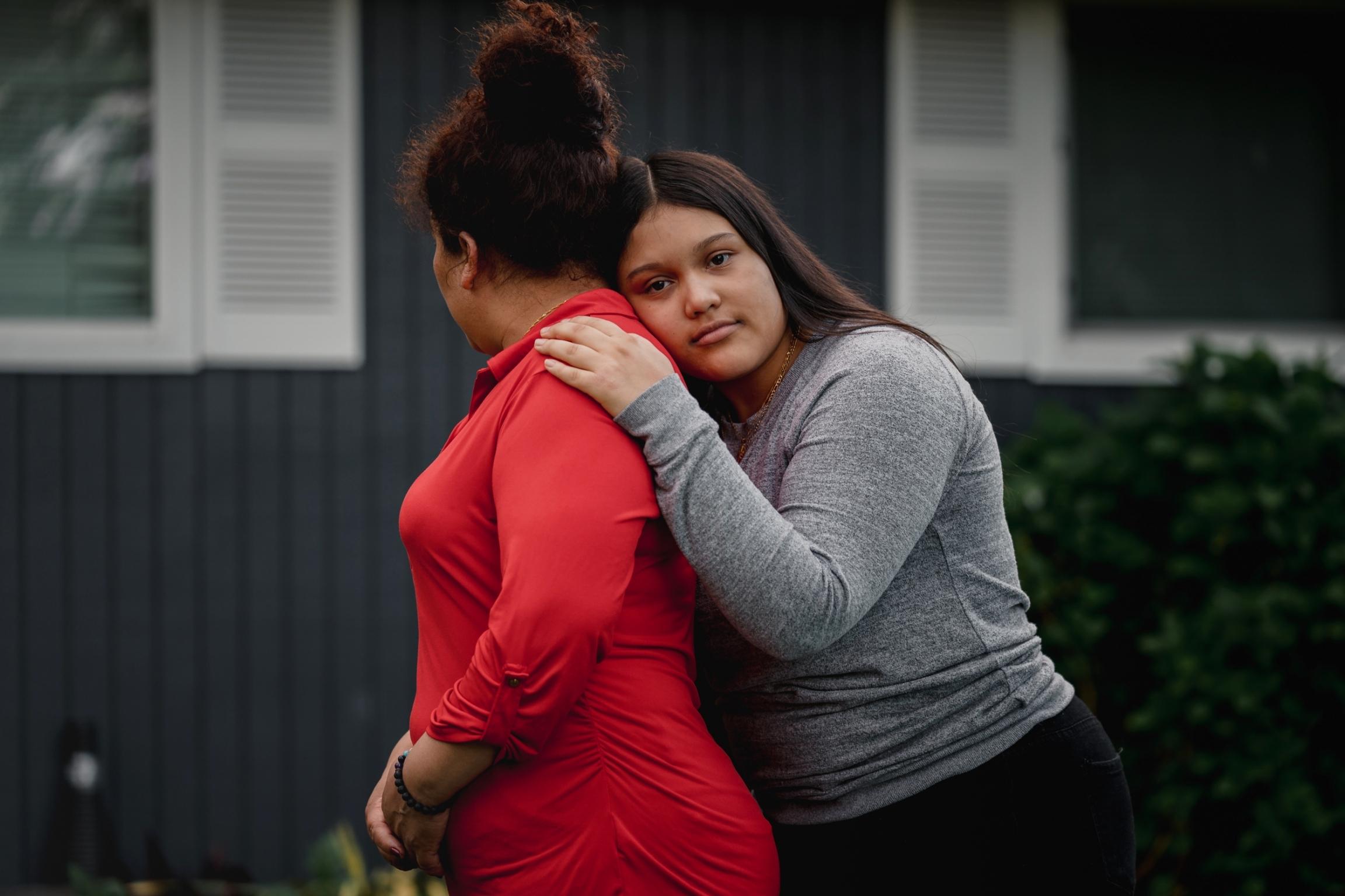Una joven abraza a su mama mientras posa para una foto.