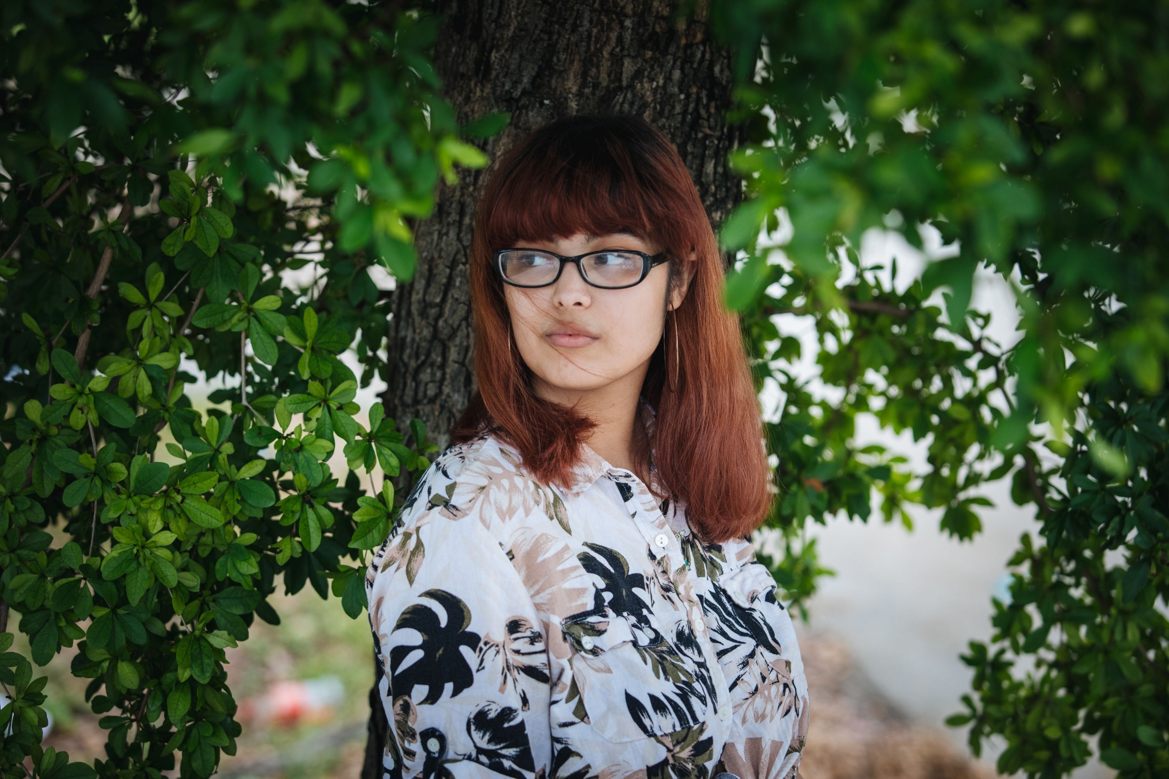 A young woman on a floral shirt posses for a photo in a garden.
