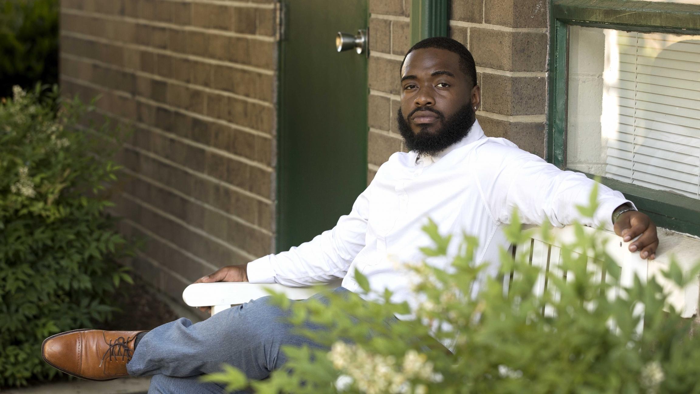 Un joven que viste una camisa blanca esta sentado en frente de una casa y posando para una foto.