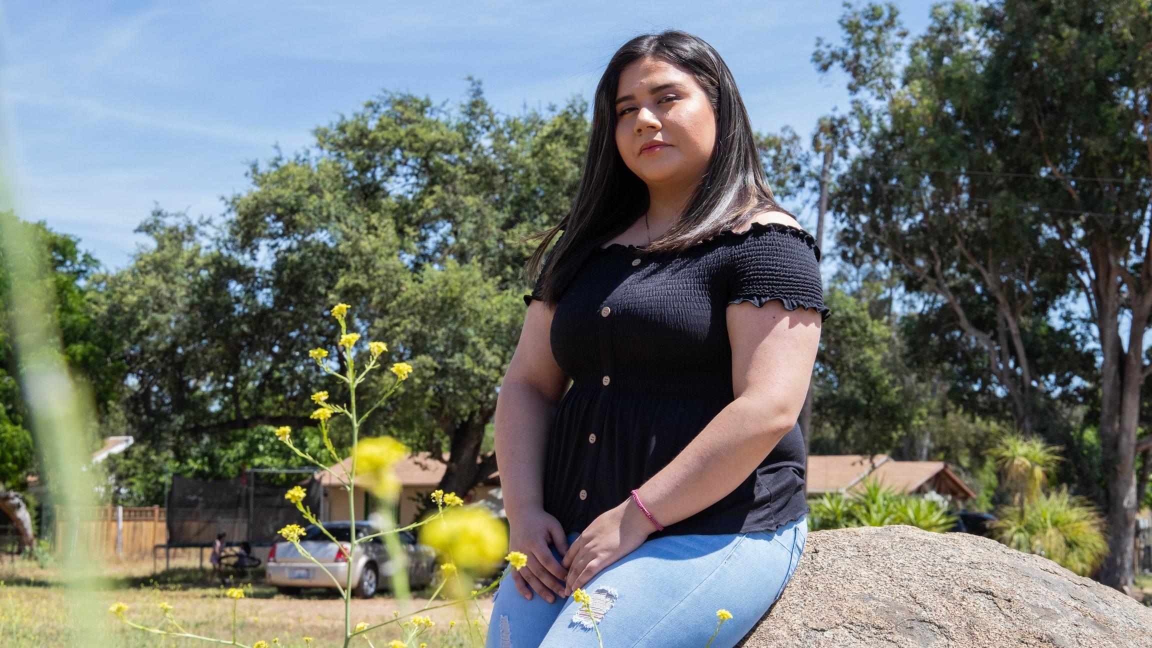 Una joven en camisa negra y jeans esta sentada en una piedra grande mientras posa para una foto.