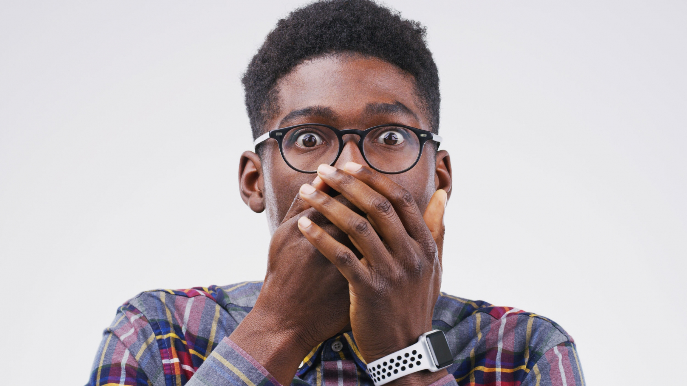 A man poses for the camera with his hands over his mouth in this stock photo