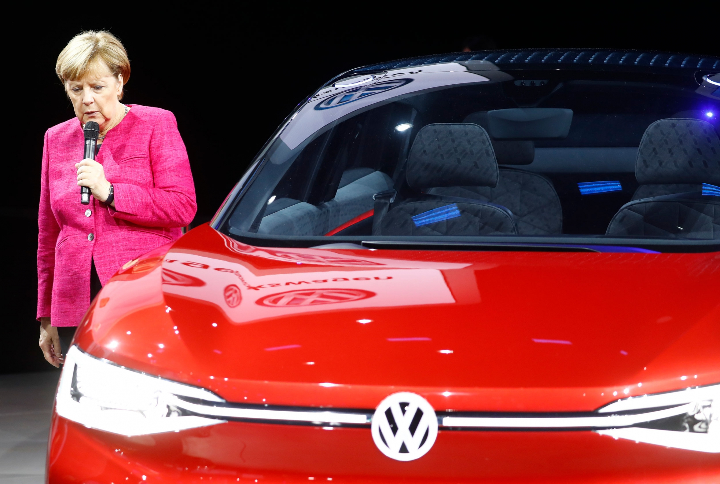 German chancellor Angela Merkel is shown wearing a pink jacket and standing next to a red VW car.
